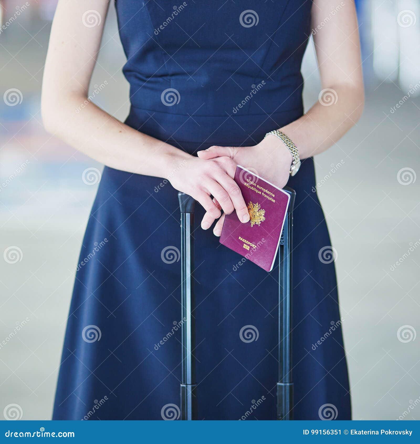 妇女在国际机场在她的手上的持法国护照