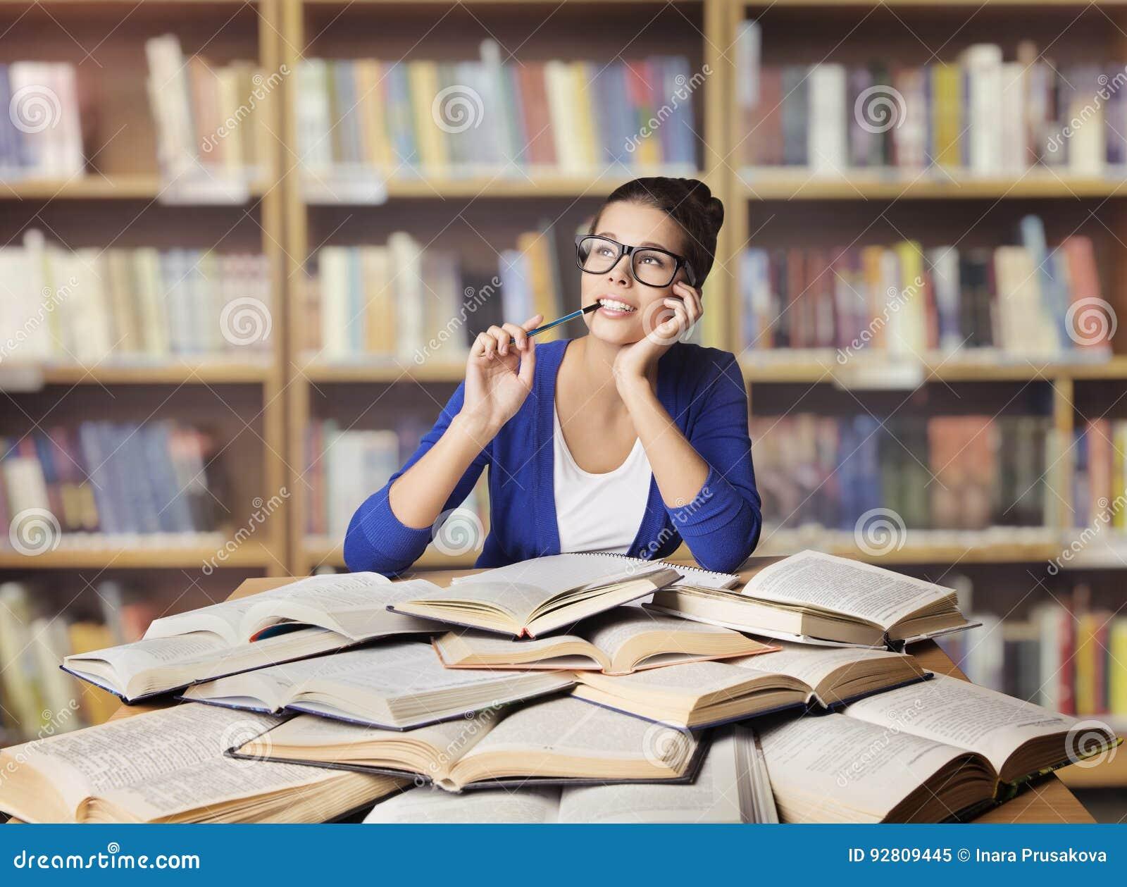 妇女在图书馆,学生研究被打开的书里,学习女孩