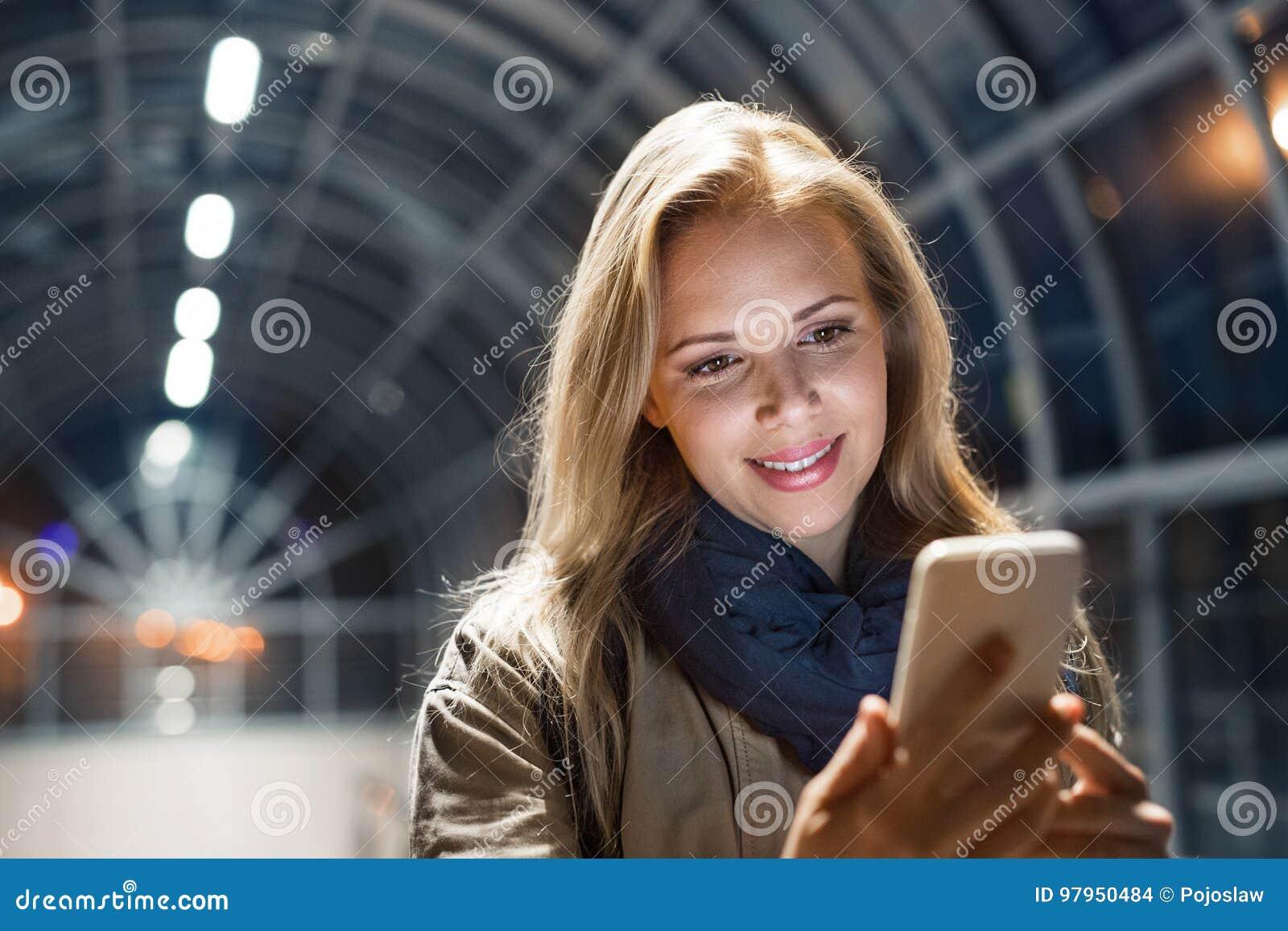 妇女在城市在拿着智能手机的晚上,发短信