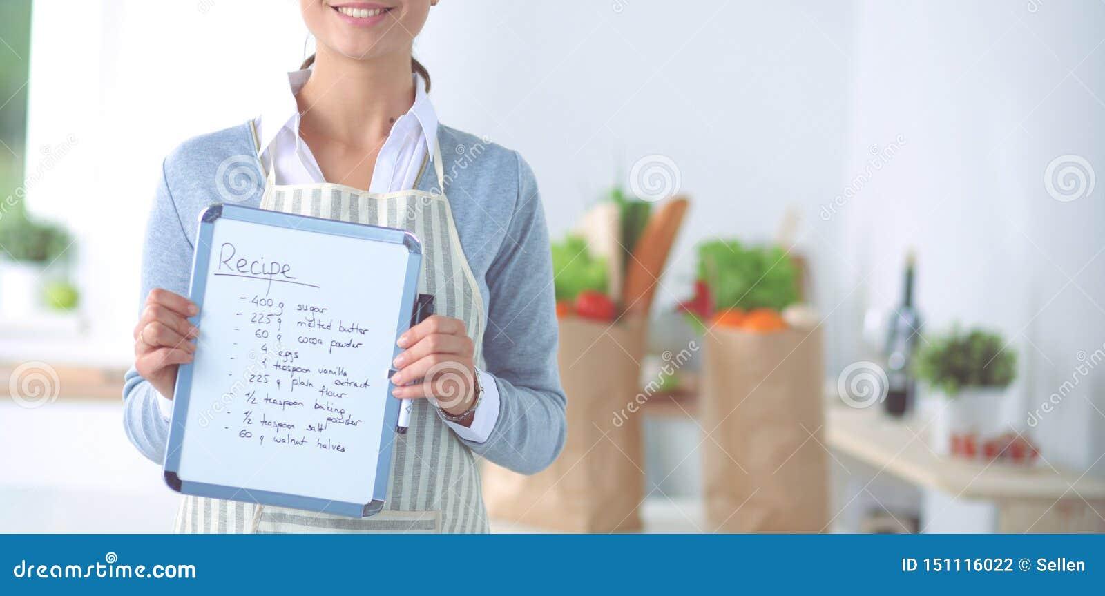 妇女在家厨房里,站立在有文件夹的书桌附近