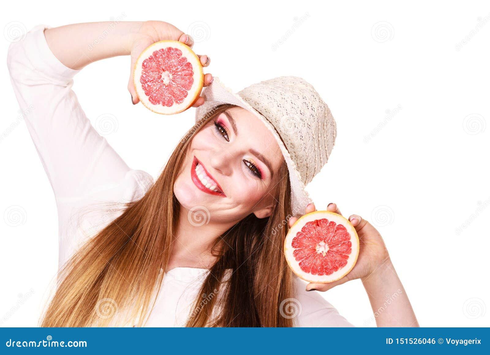 妇女在手上拿着葡萄柚柑桔两halfs