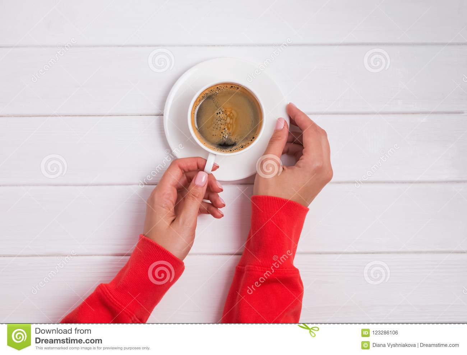 妇女在拿着一杯咖啡在白色木桌上的红色衣物的` s手