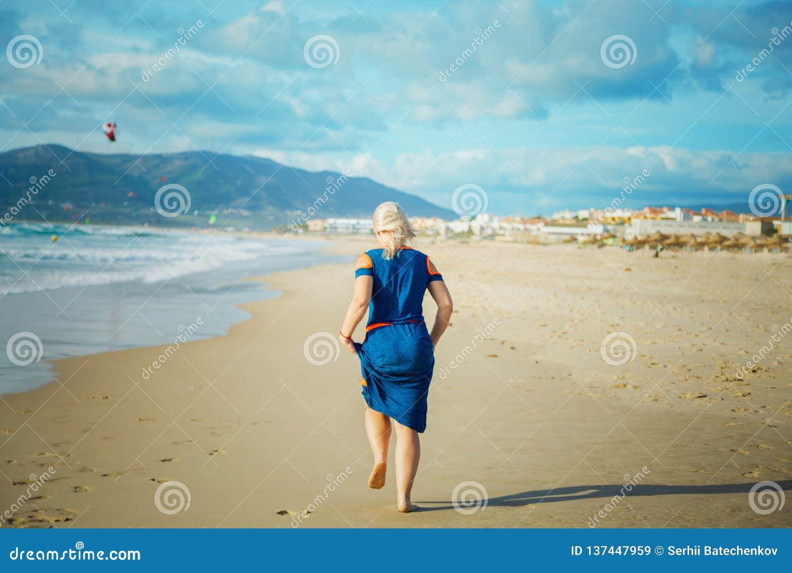 妇女在沙滩跑