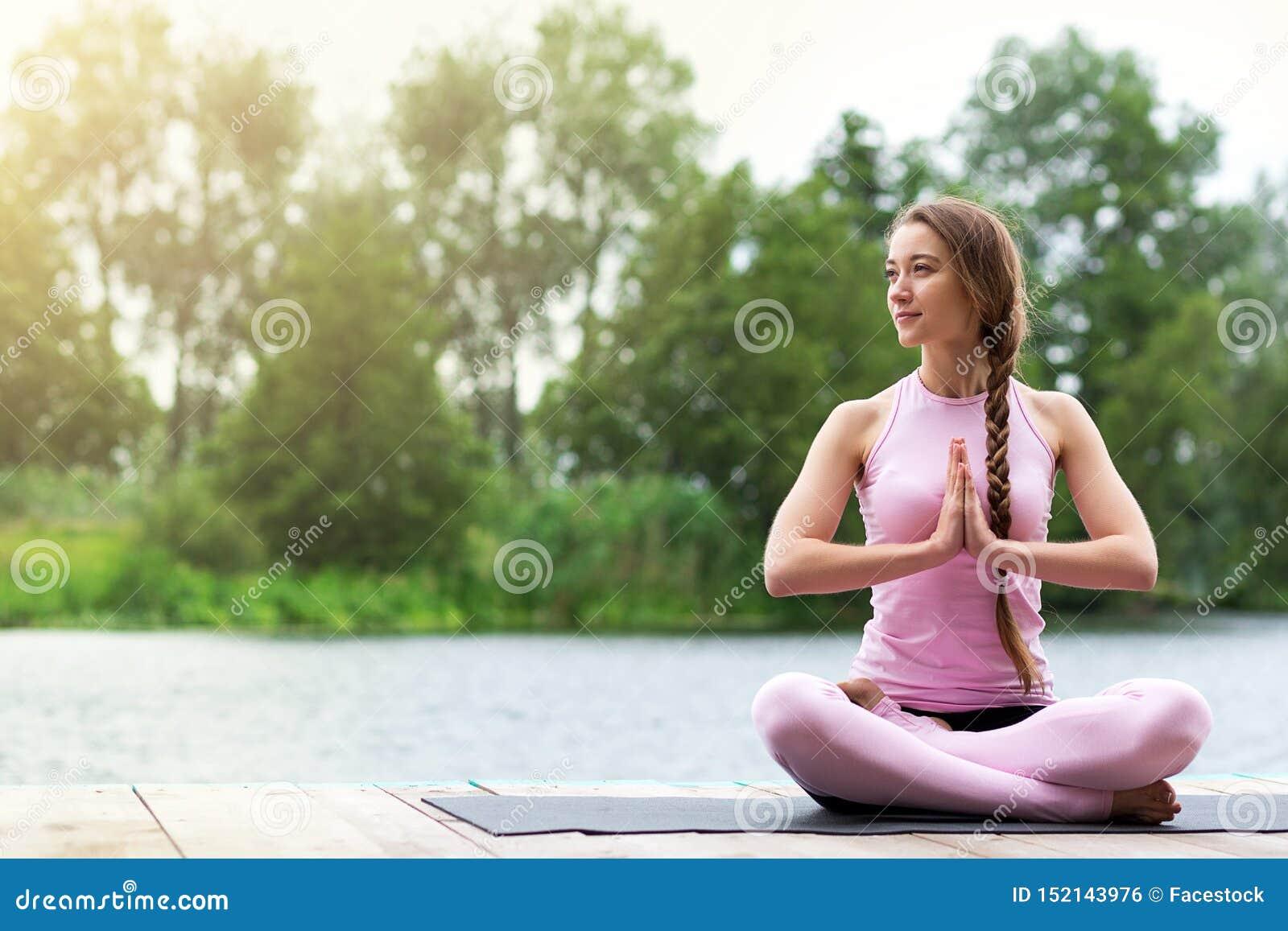 妇女在河附近实践瑜伽 凝思本质上 r