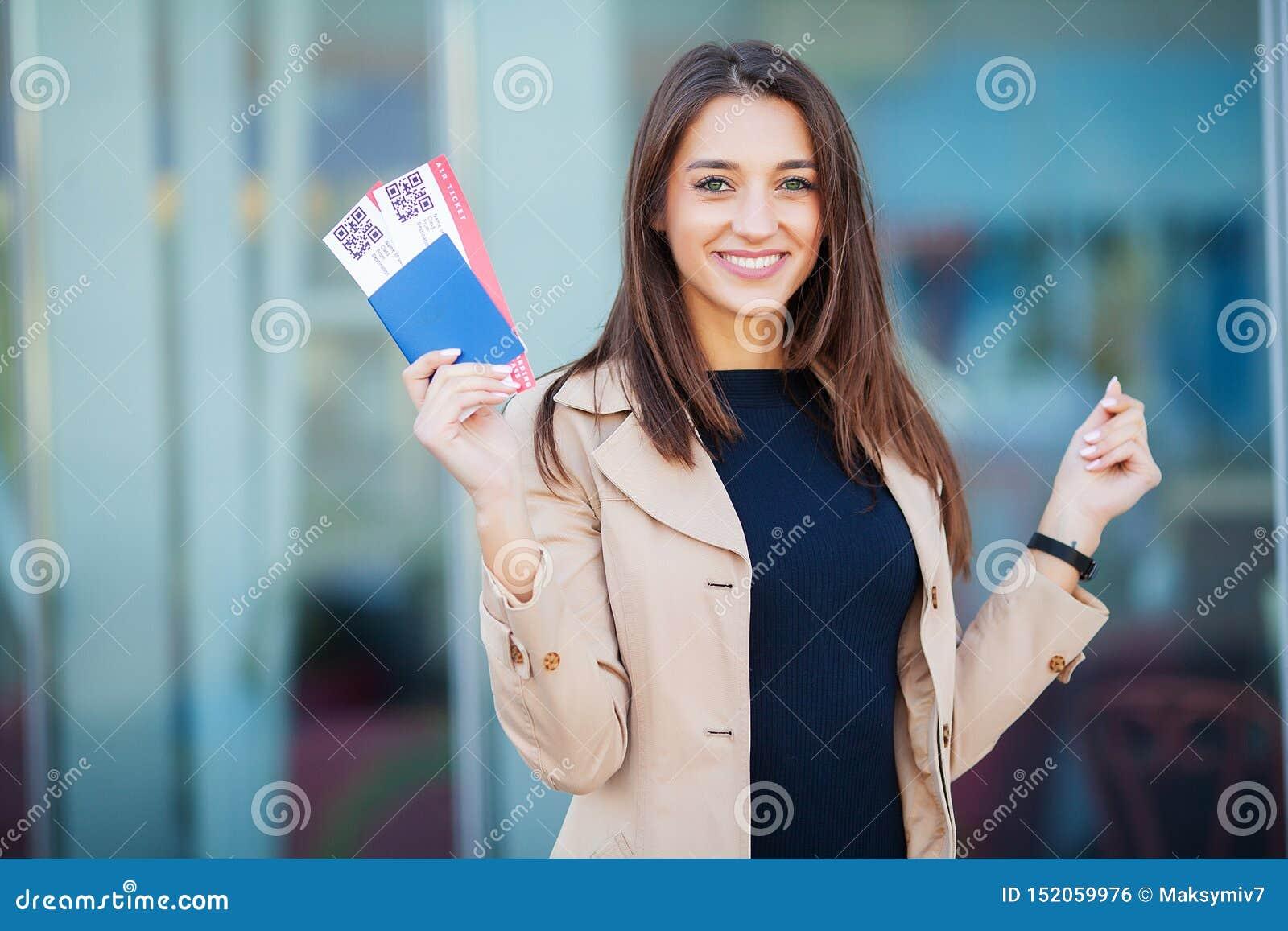 ?? 妇女在海外护照的藏品两机票在机场附近
