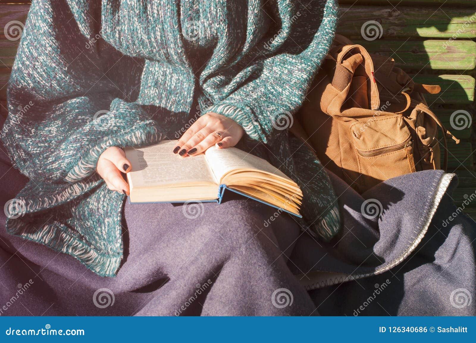 妇女在秋天编织了用外面温暖的格子花呢披肩读书盖的衣裳,在木跷跷板的开会