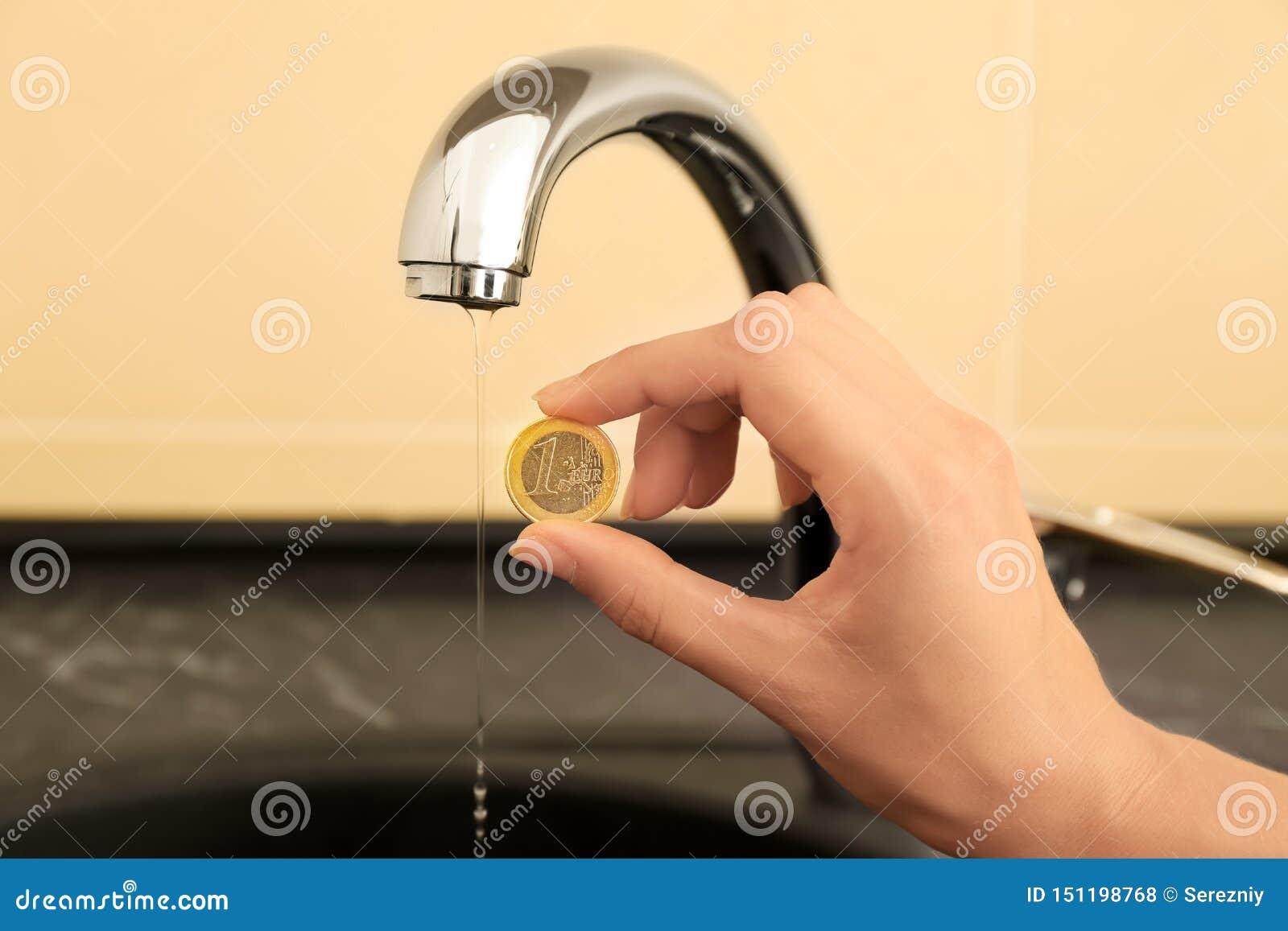 妇女在金属轻拍附近的藏品硬币 水挽救概念