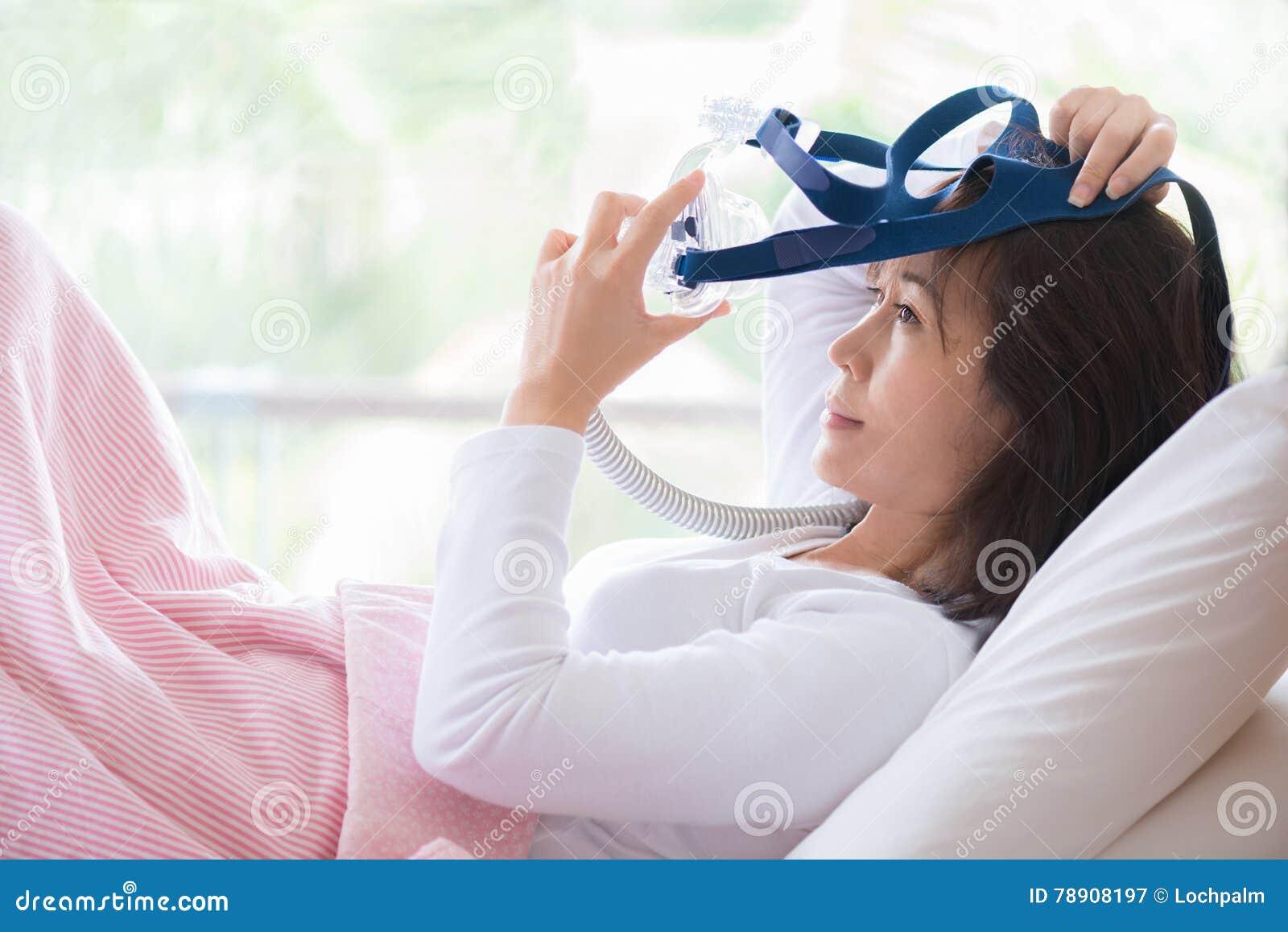 妇女在戴着CPAP面具,睡眠停吸疗法的床上放置