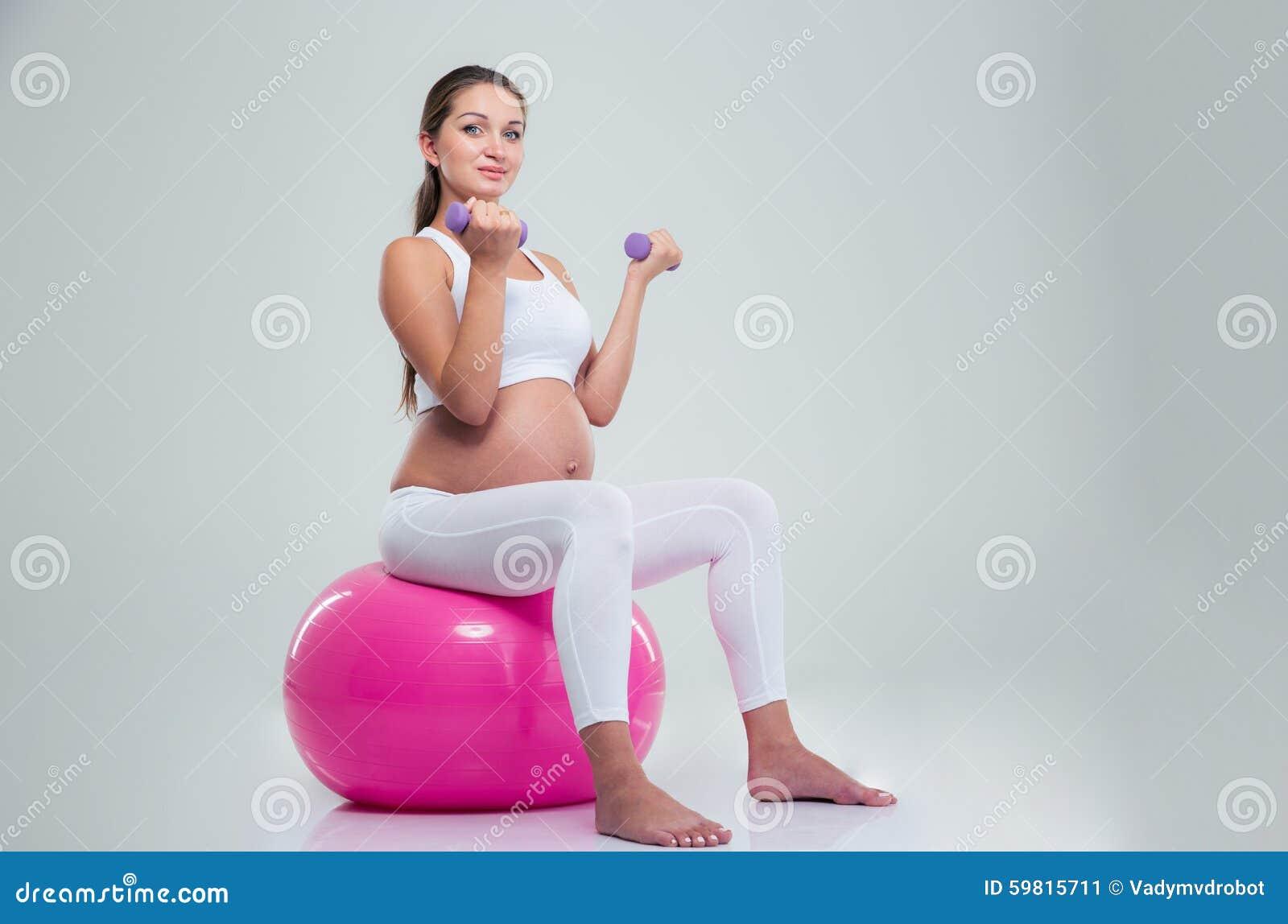 妇女坐健身球和锻炼与哑铃