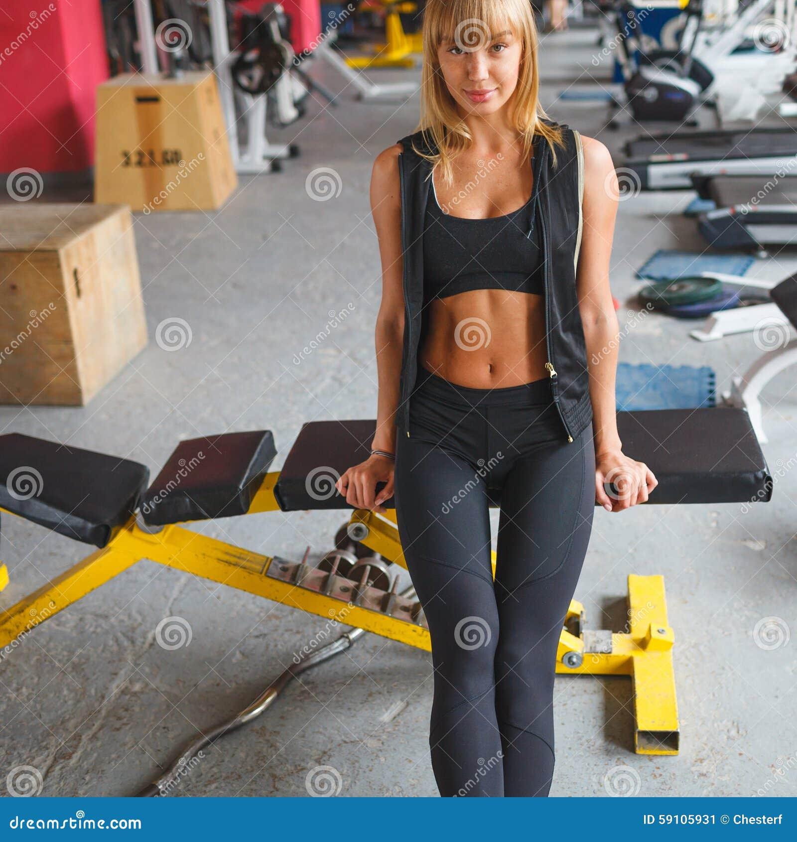 妇女坐在健身房的一条长凳