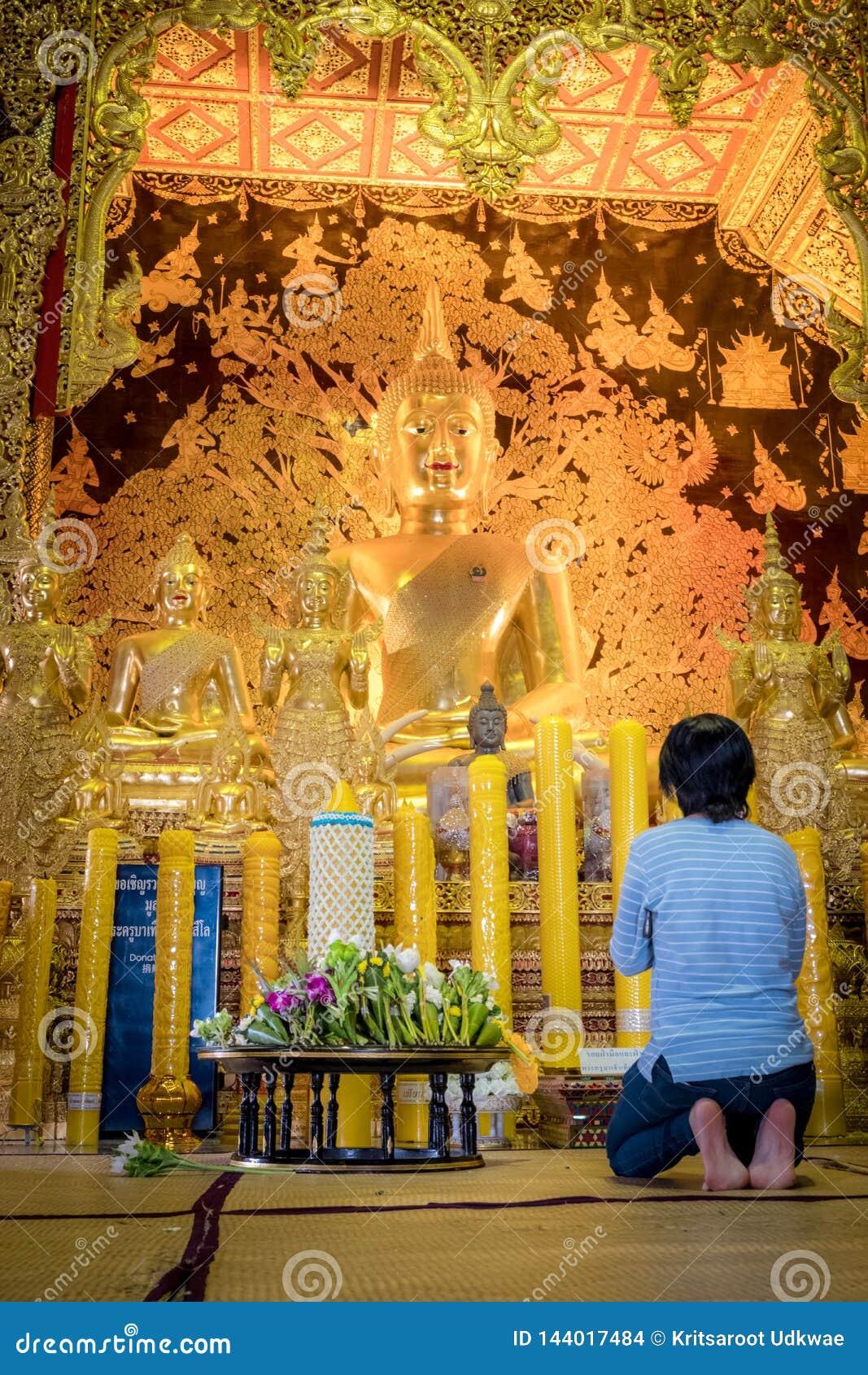 妇女坐在泰国寺庙名为'Wat小室Salee斯里Muang淦Wat禁令小室前面'金黄菩萨雕象祈祷
