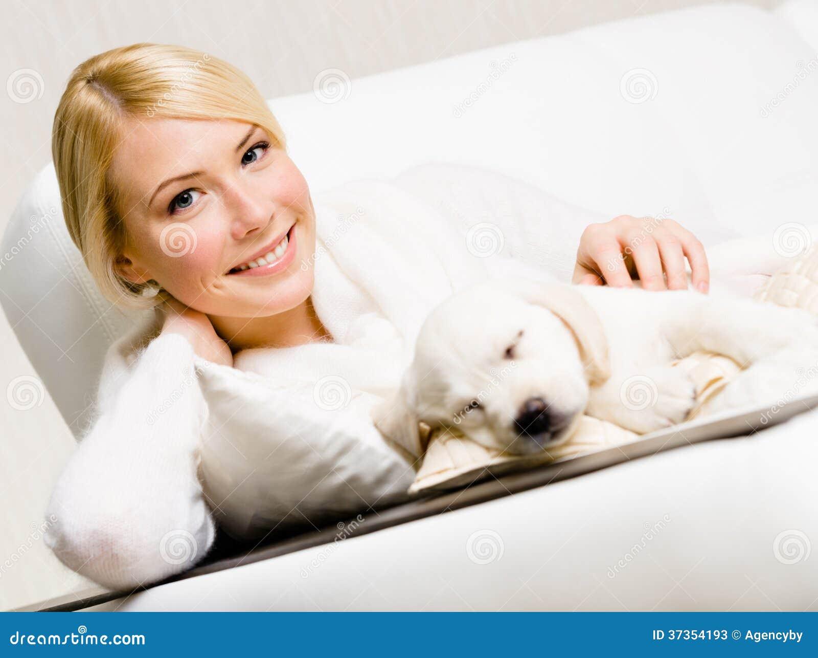 妇女坐有睡觉小狗的沙发
