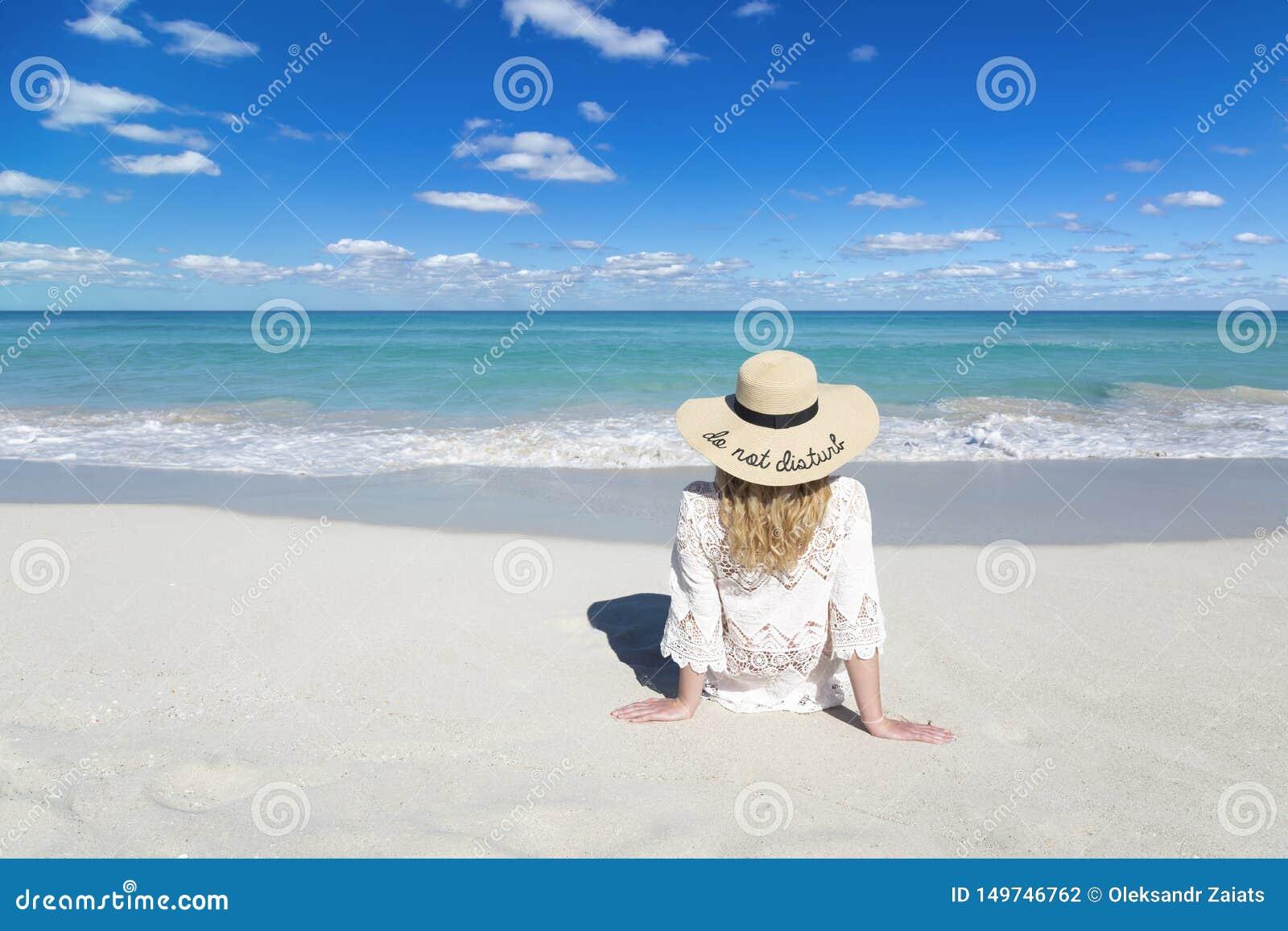 妇女坐海洋海滩在古巴,佩带的帽子,美丽的天空,并且水,不干扰,完善的背景,自由空间