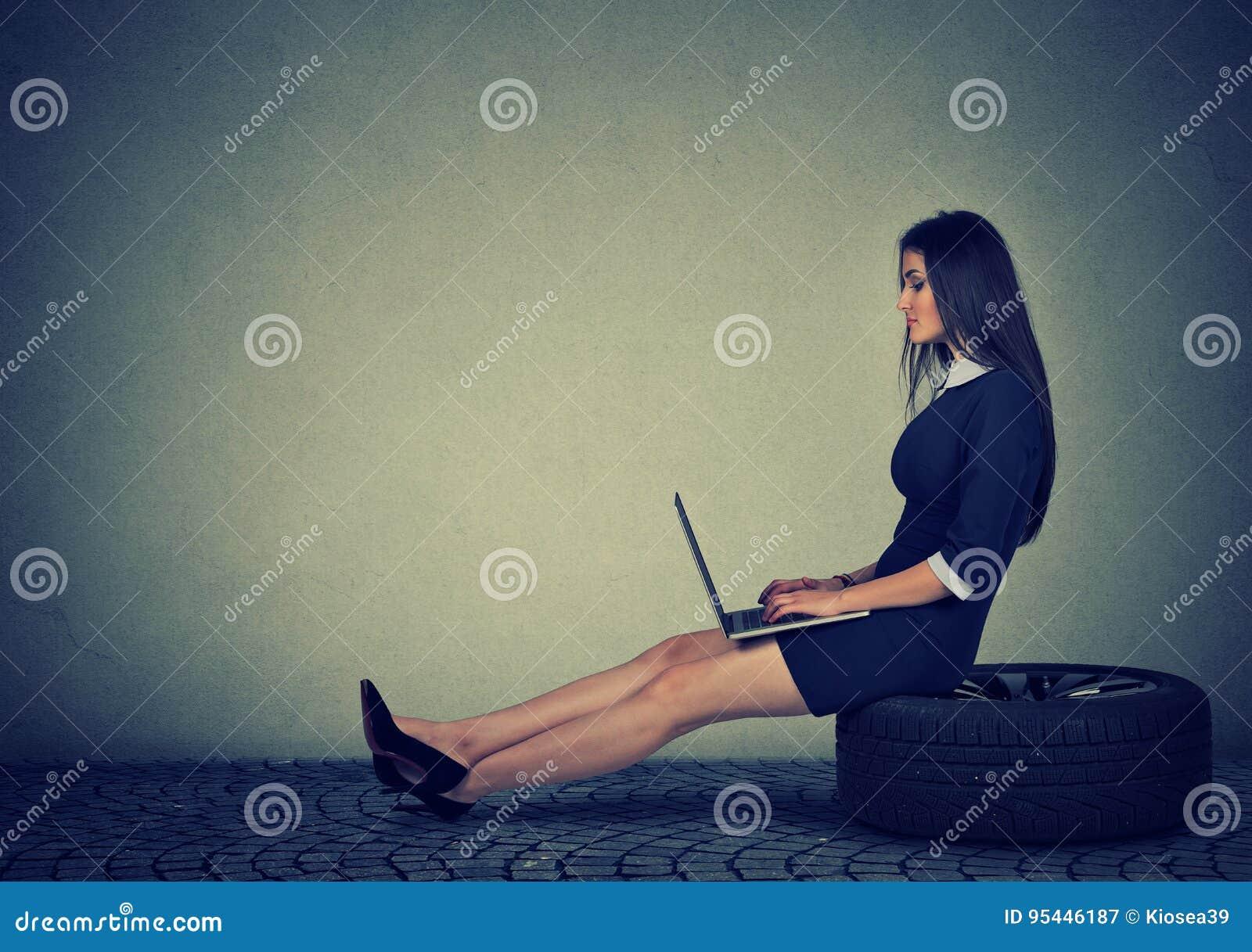 妇女坐研究膝上型计算机的车胎