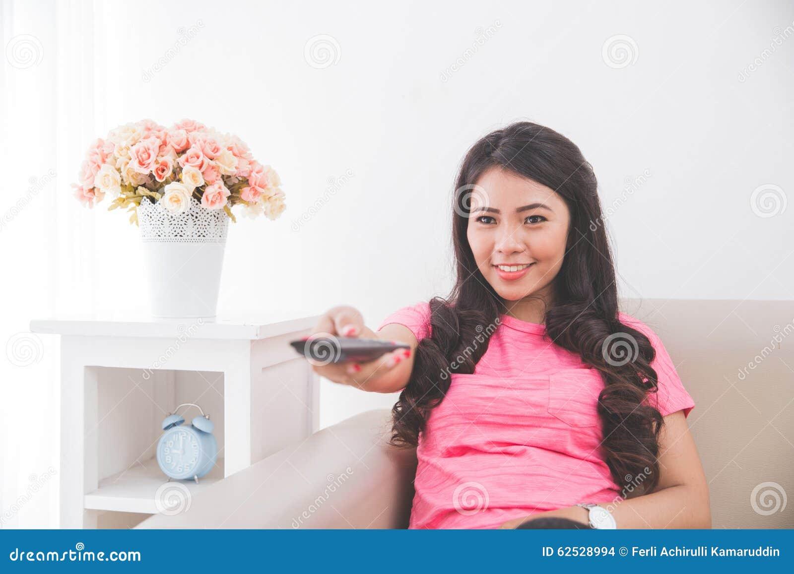 妇女坐长沙发,使用遥控
