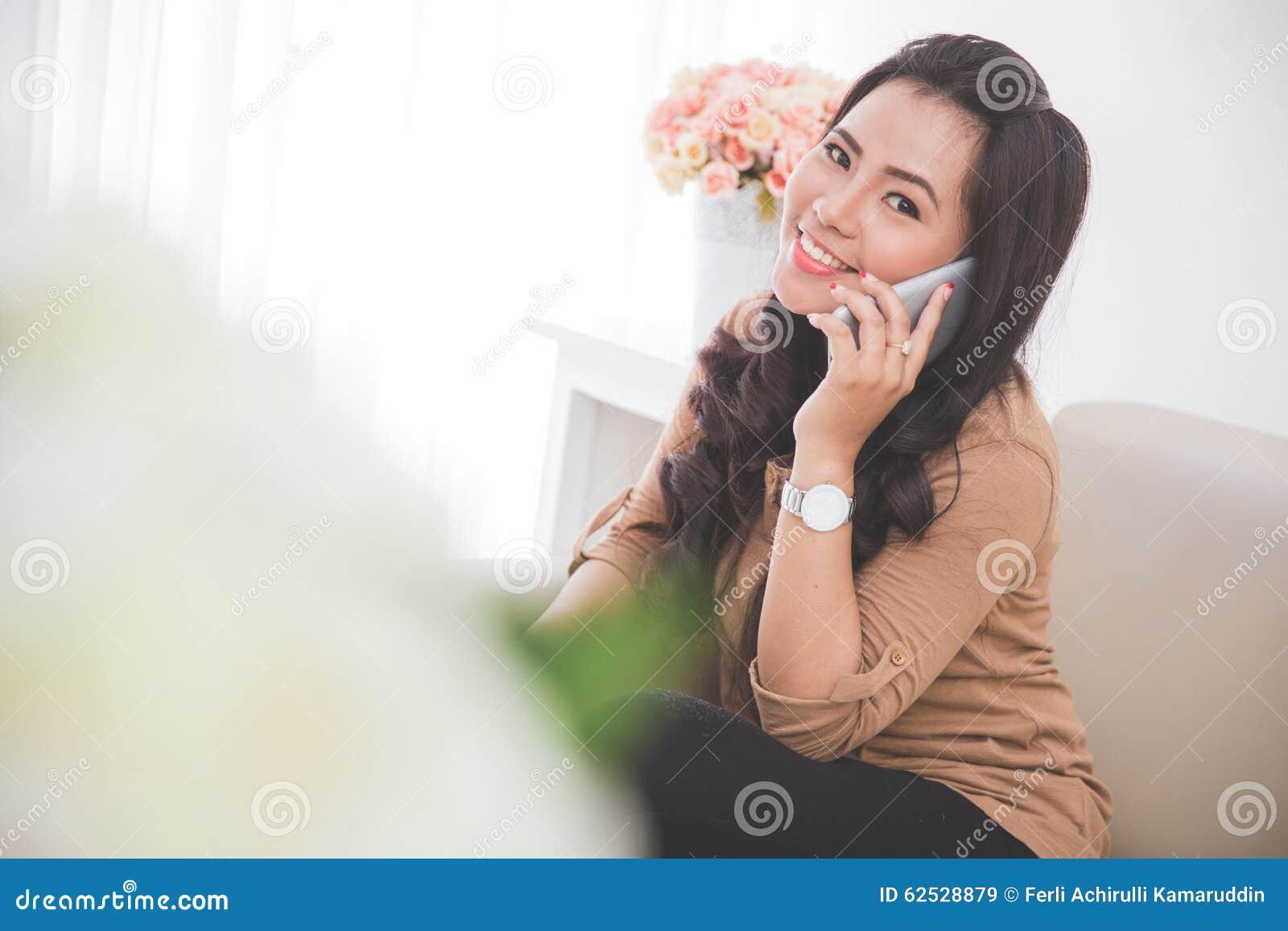 妇女坐长沙发,告诉有智能手机的朋友