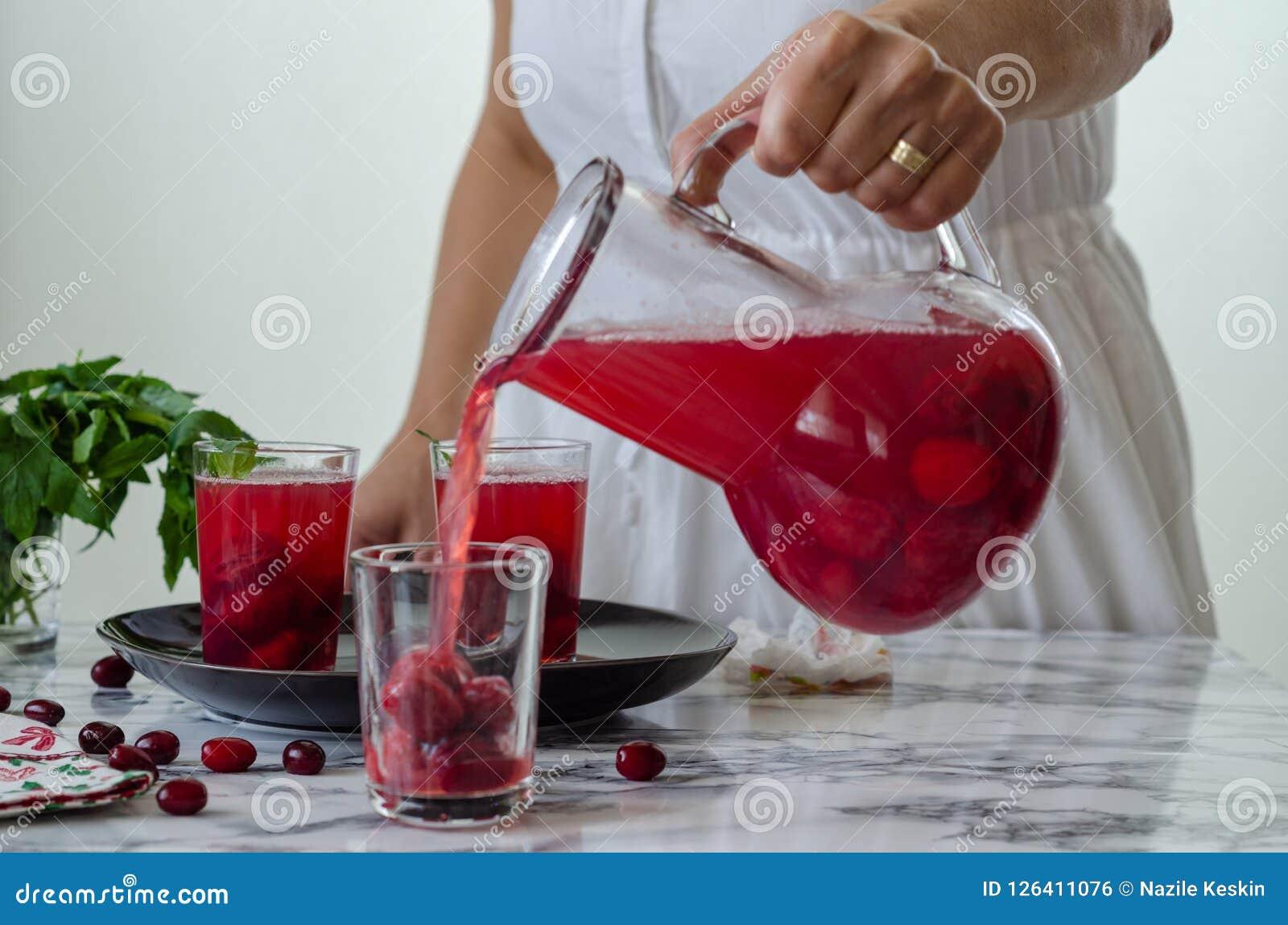 妇女填装在玻璃的蔓越橘汁