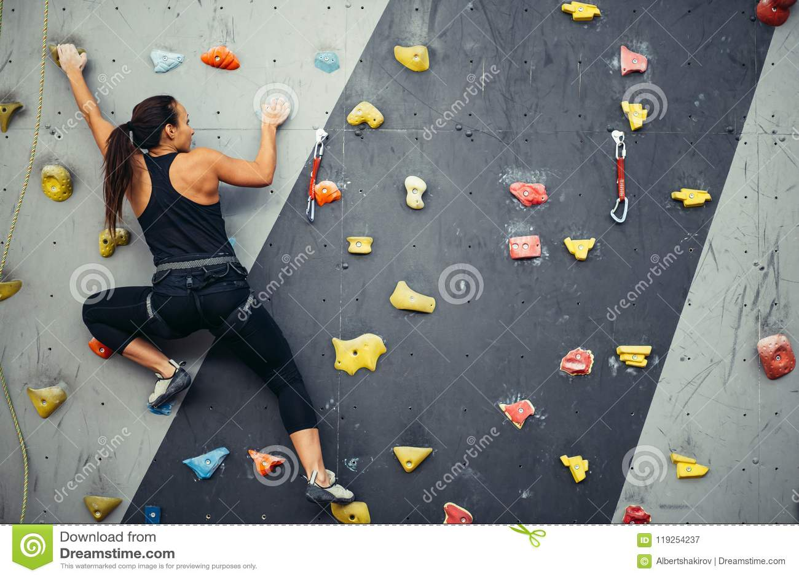 妇女实践的攀岩在人为墙壁上户内 活跃生活方式和bouldering的概念