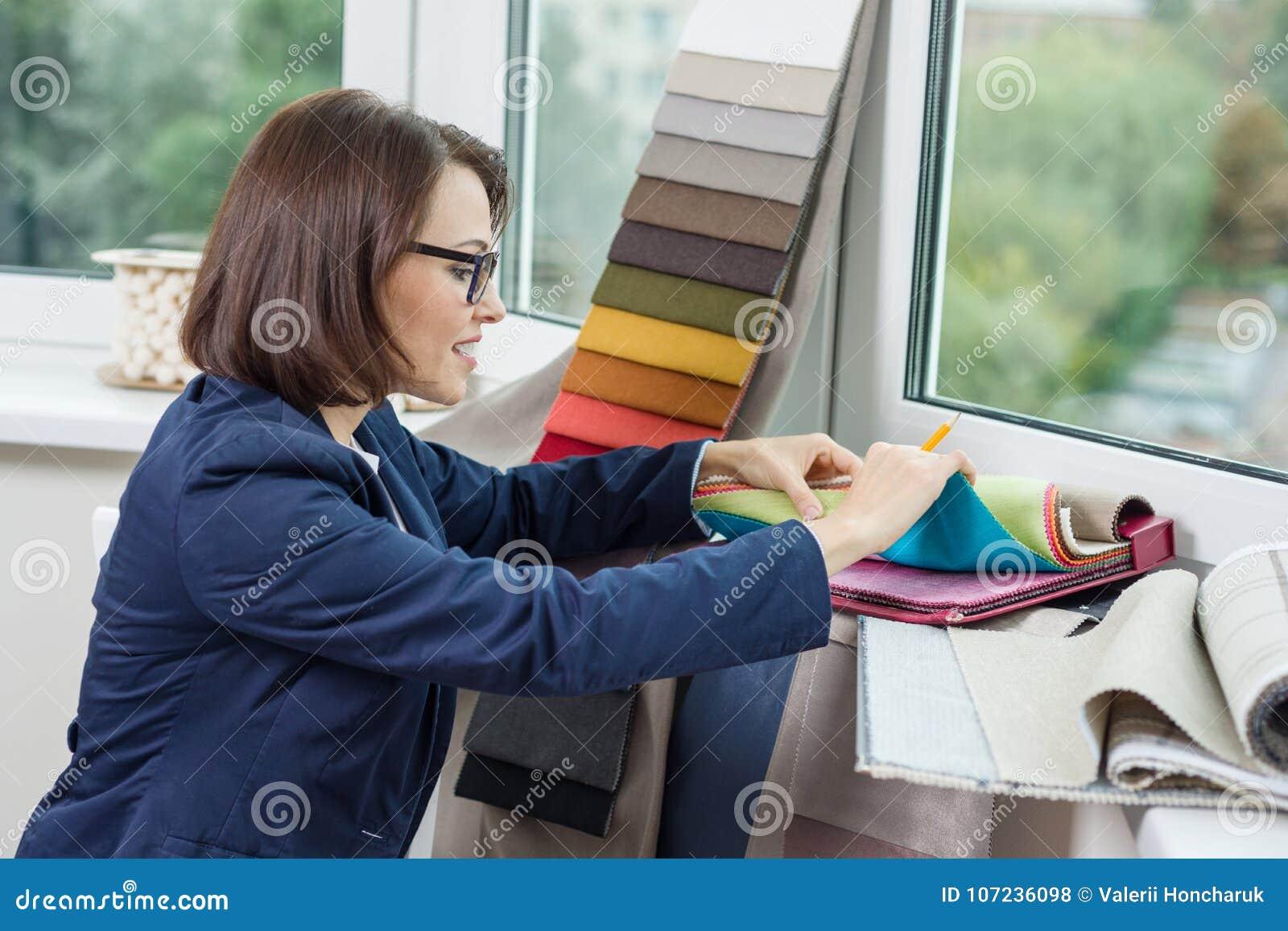 妇女室内设计师、与织品一起使用样品帷幕的和窗帘