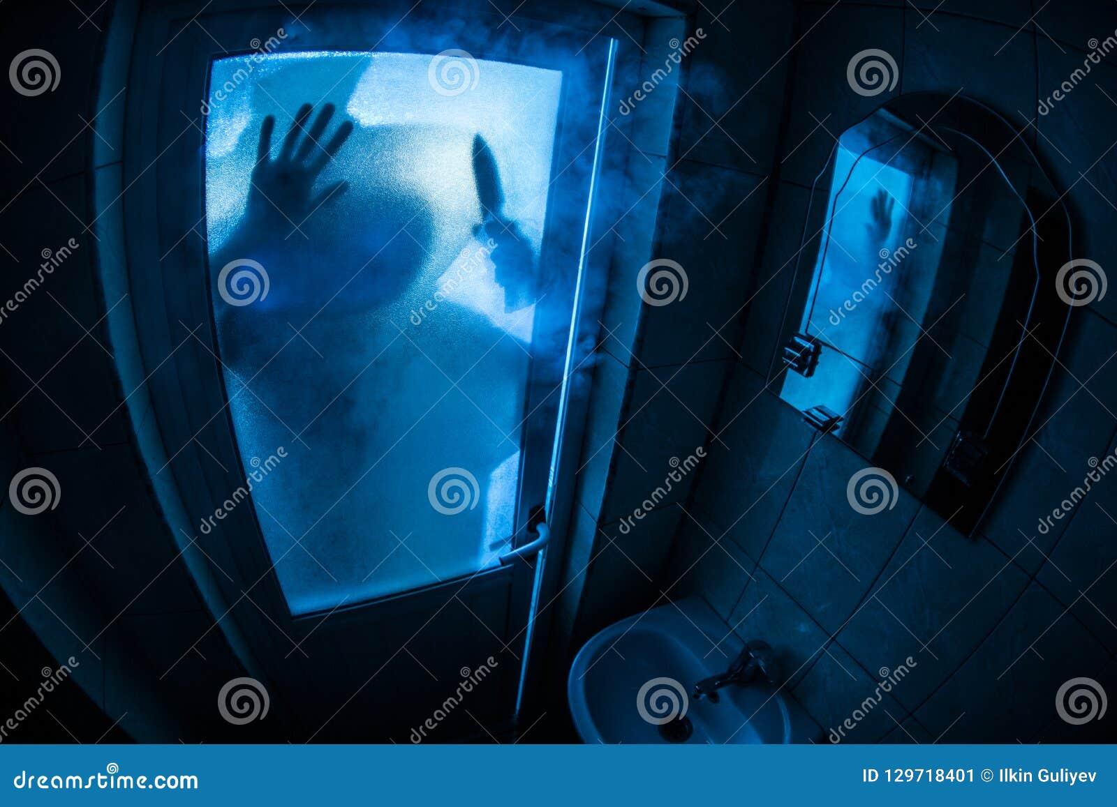 妇女恐怖剪影在窗口里 可怕巫婆万圣节概念被弄脏的剪影在卫生间里 选择聚焦