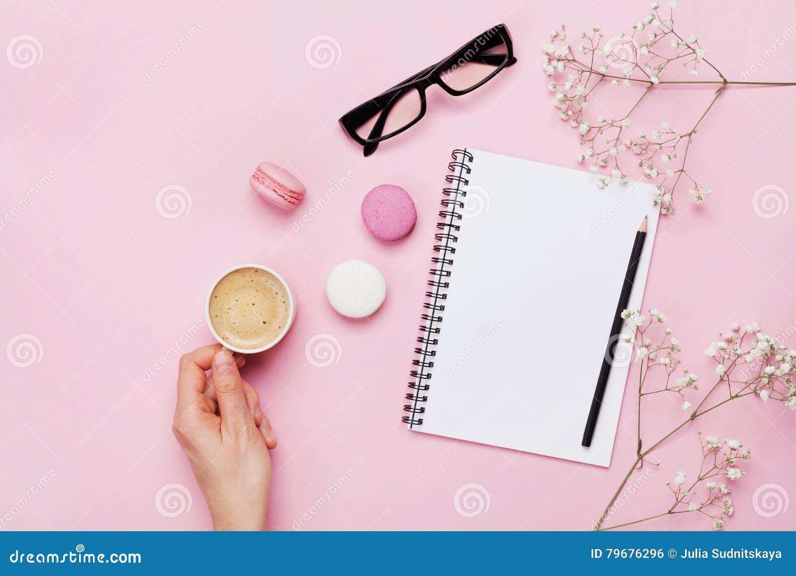 妇女手举行咖啡、蛋糕macaron、干净的笔记本、镜片和花在桃红色桌上从上面 女性运转的书桌