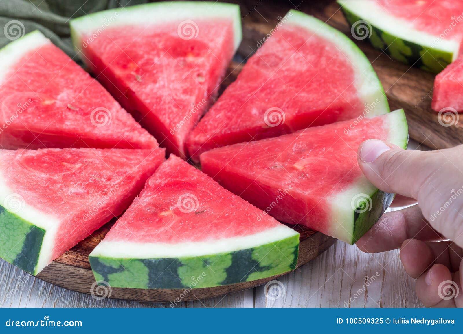 妇女手作为切片新鲜的无核的西瓜削减了成三角放置在一块木板材的形状,水平