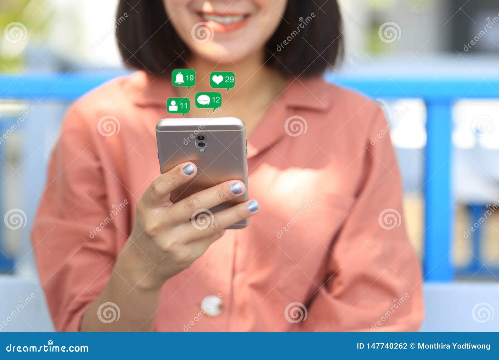 妇女手检查的社会媒介藏品智能手机与象或全息图在咖啡馆,通讯网络互联网和