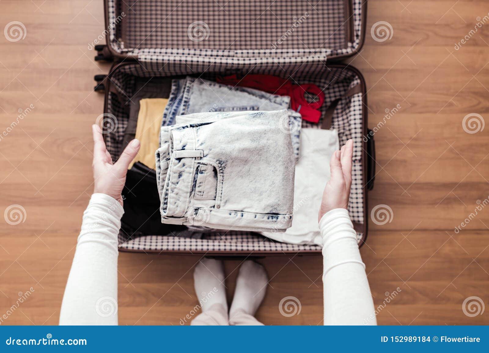 妇女手顶视图包装一次新的旅途的一件行李