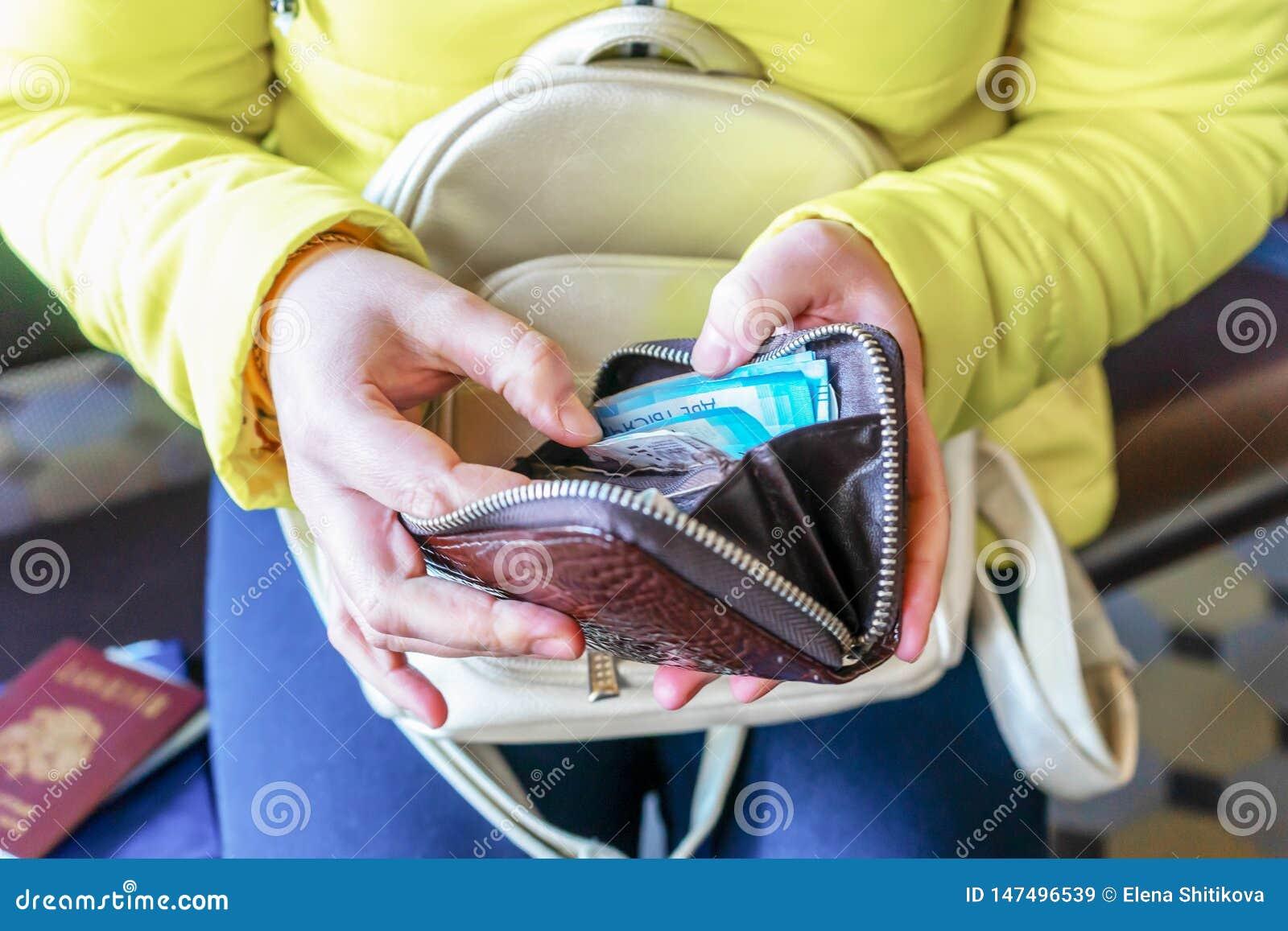 妇女拿着一个钱包并且计数俄国金钱