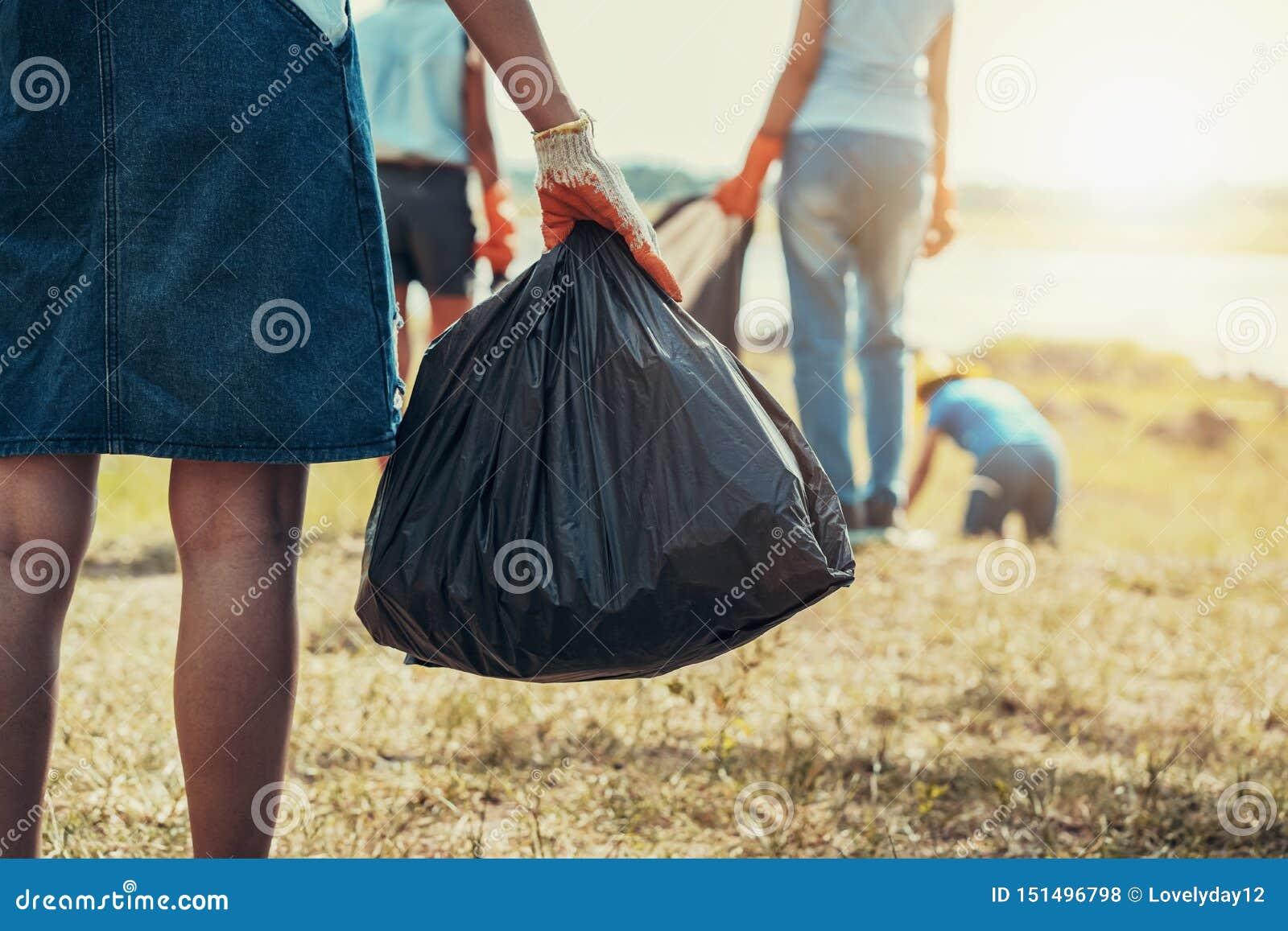 妇女拿着黑袋子的手拾起垃圾的和手在公园