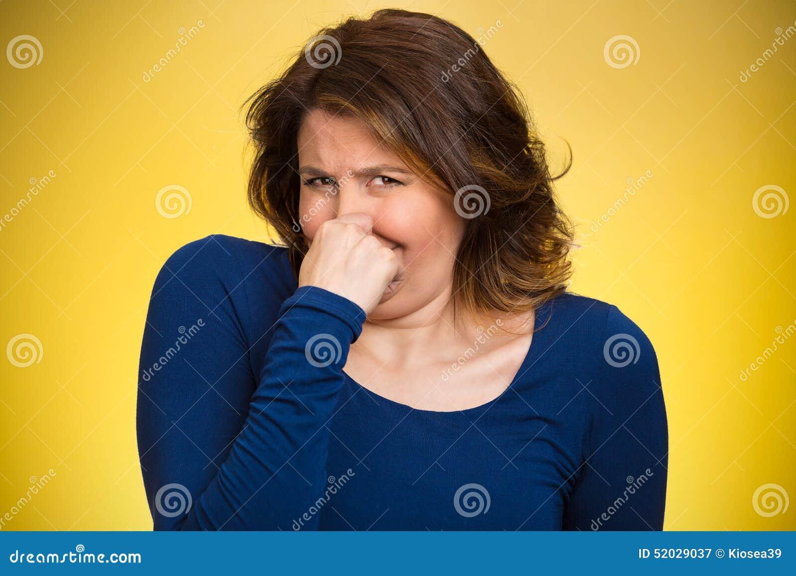 妇女捏她的鼻子,难闻的气味