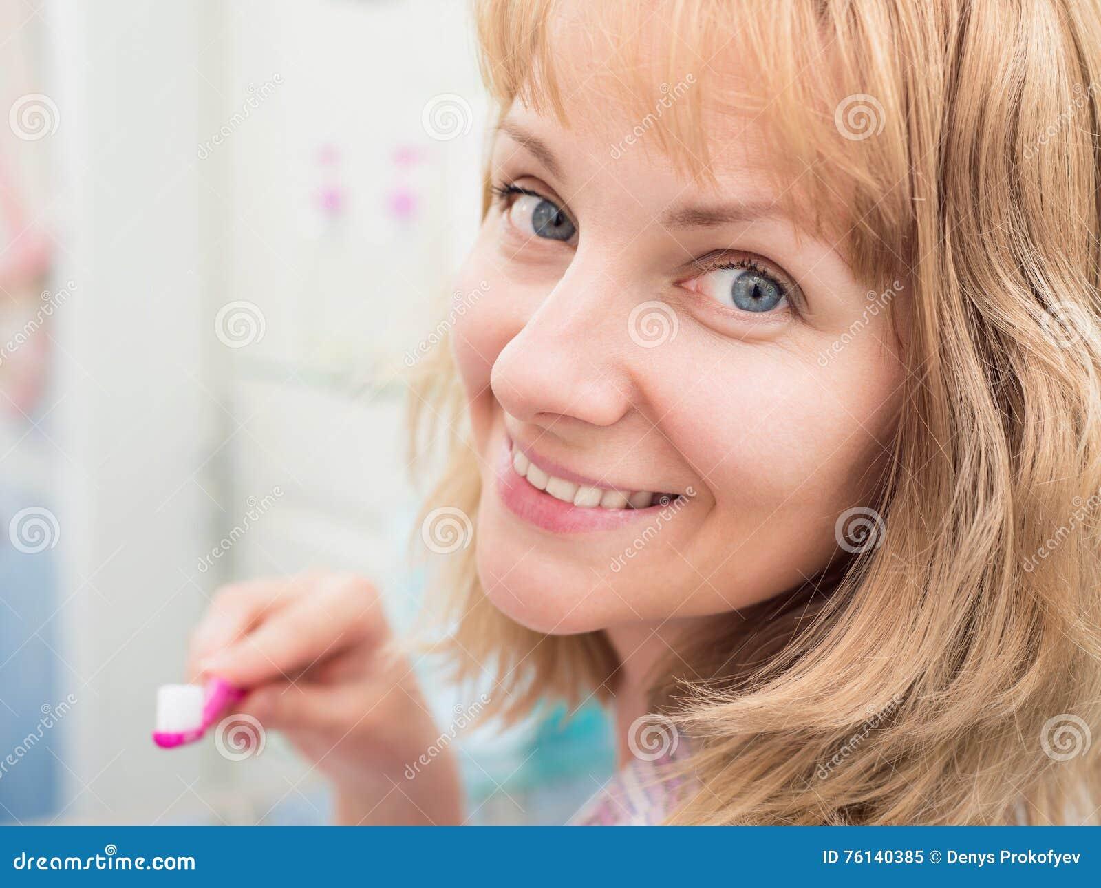 妇女掠过的牙在卫生间里