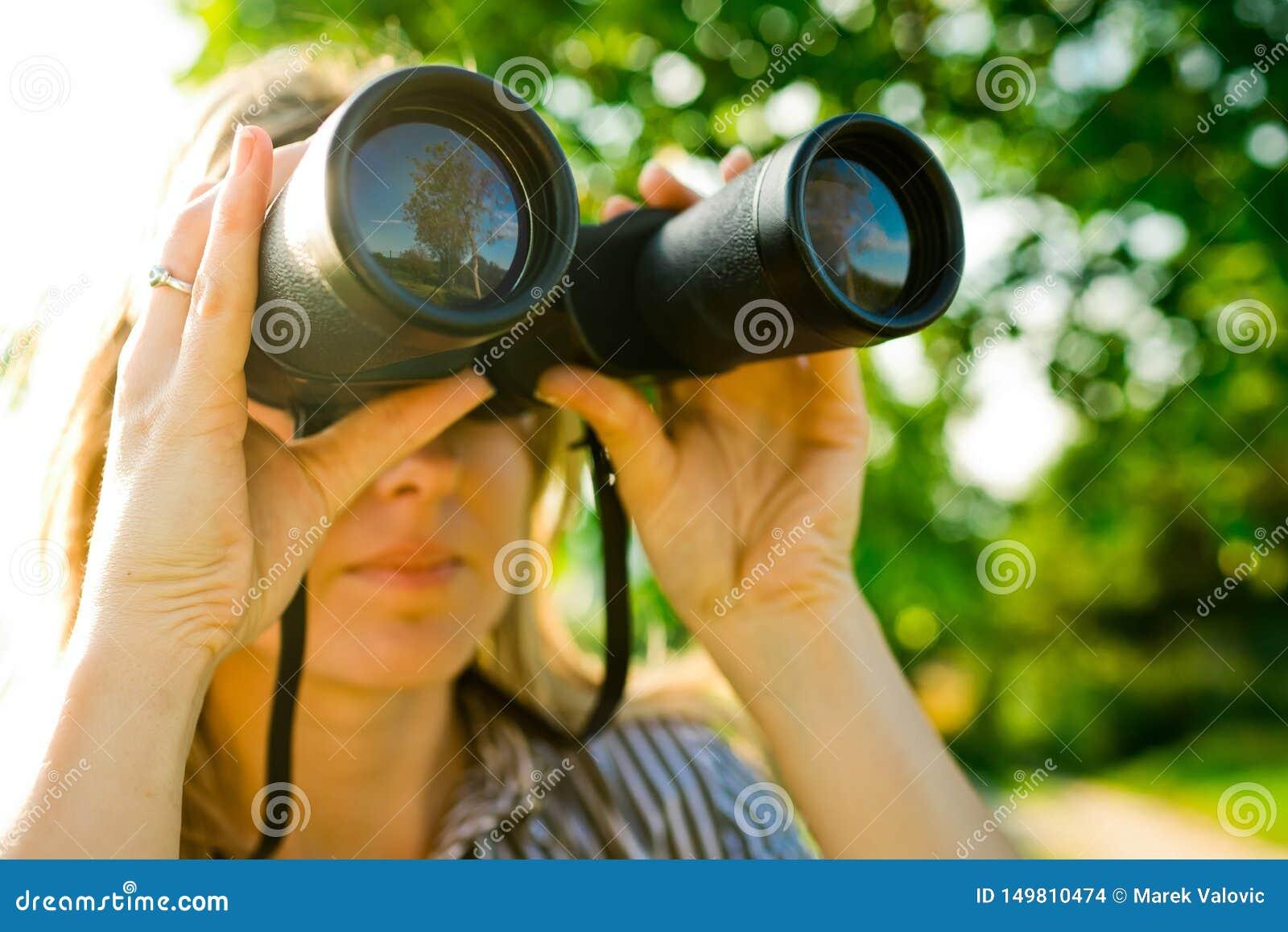 妇女探险家使用室外黑的双筒望远镜-