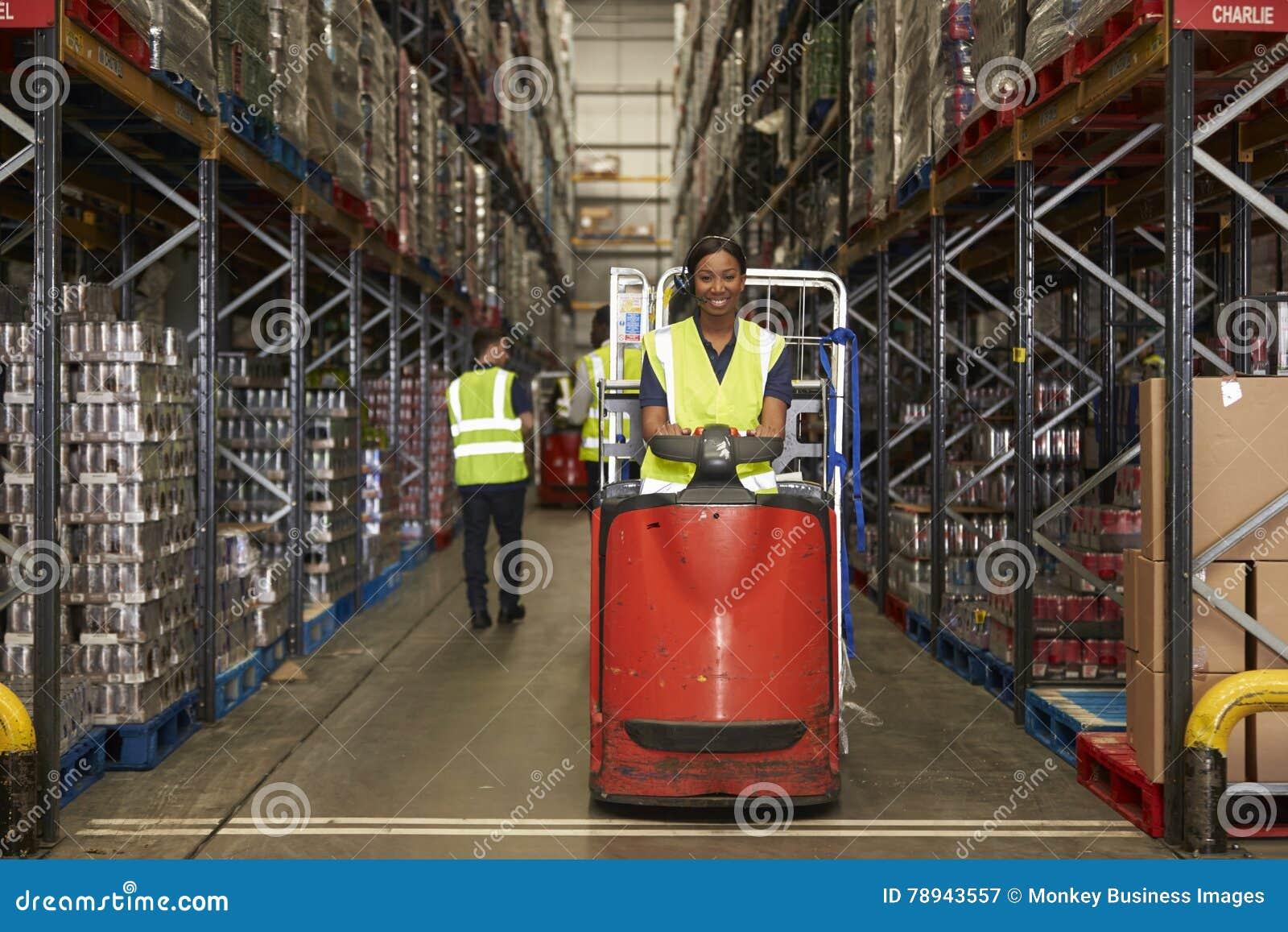 妇女操作拖曳拖拉机在繁忙的配给物仓库里