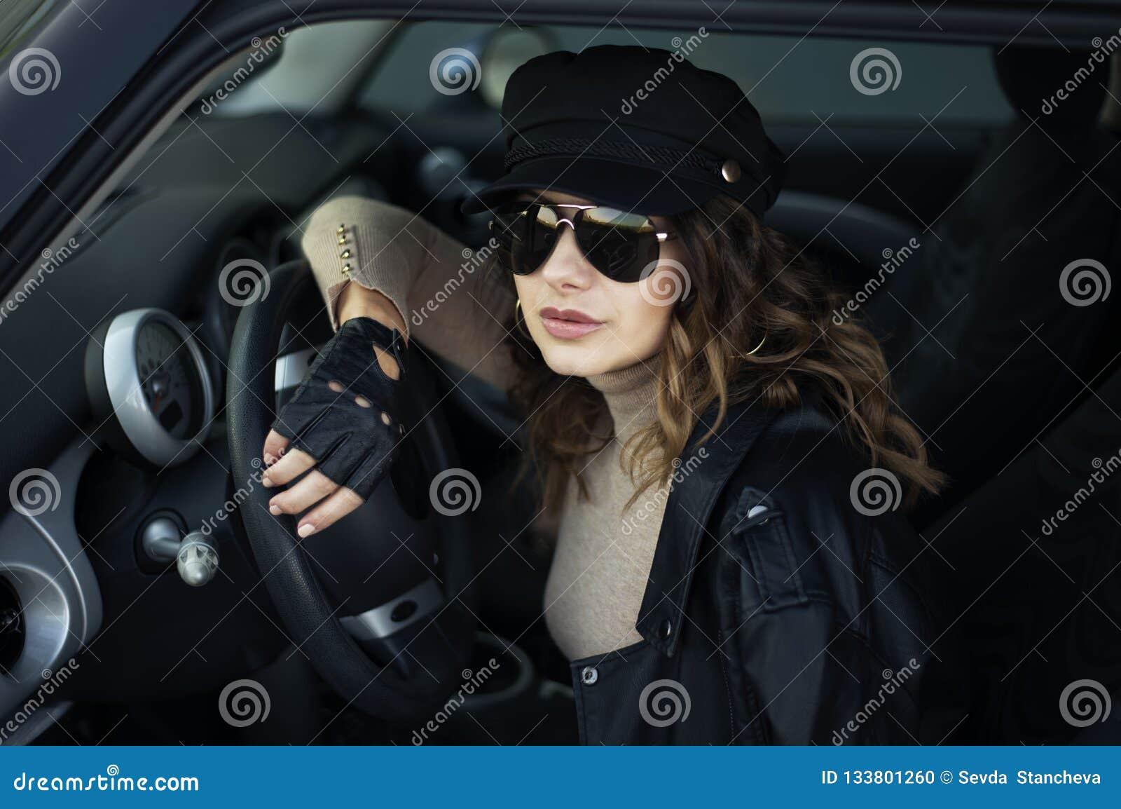 妇女时尚室外照片有黑发的在黑摆在减速火箭的汽车的皮夹克和太阳镜