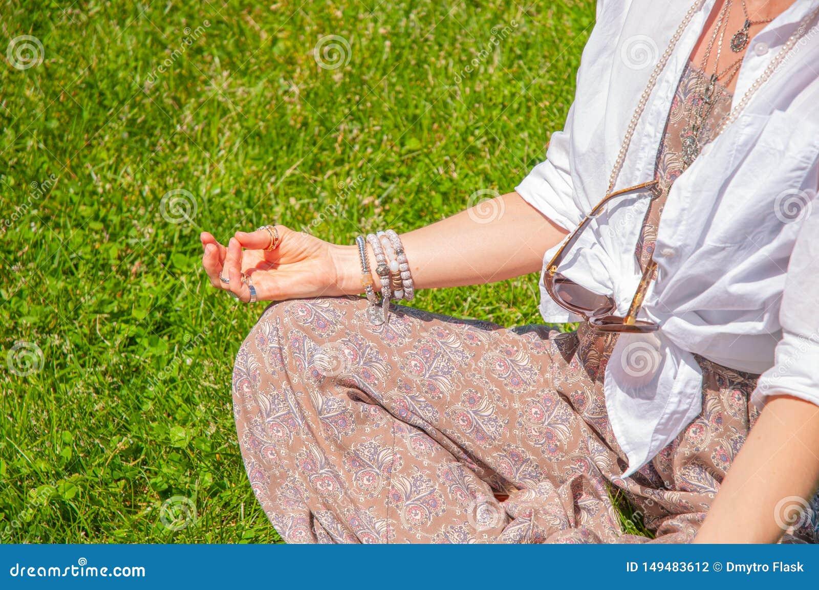 妇女是在莲花姿势的思考的开会在草在公园 与辅助部件、圆环和镯子的Boho样式