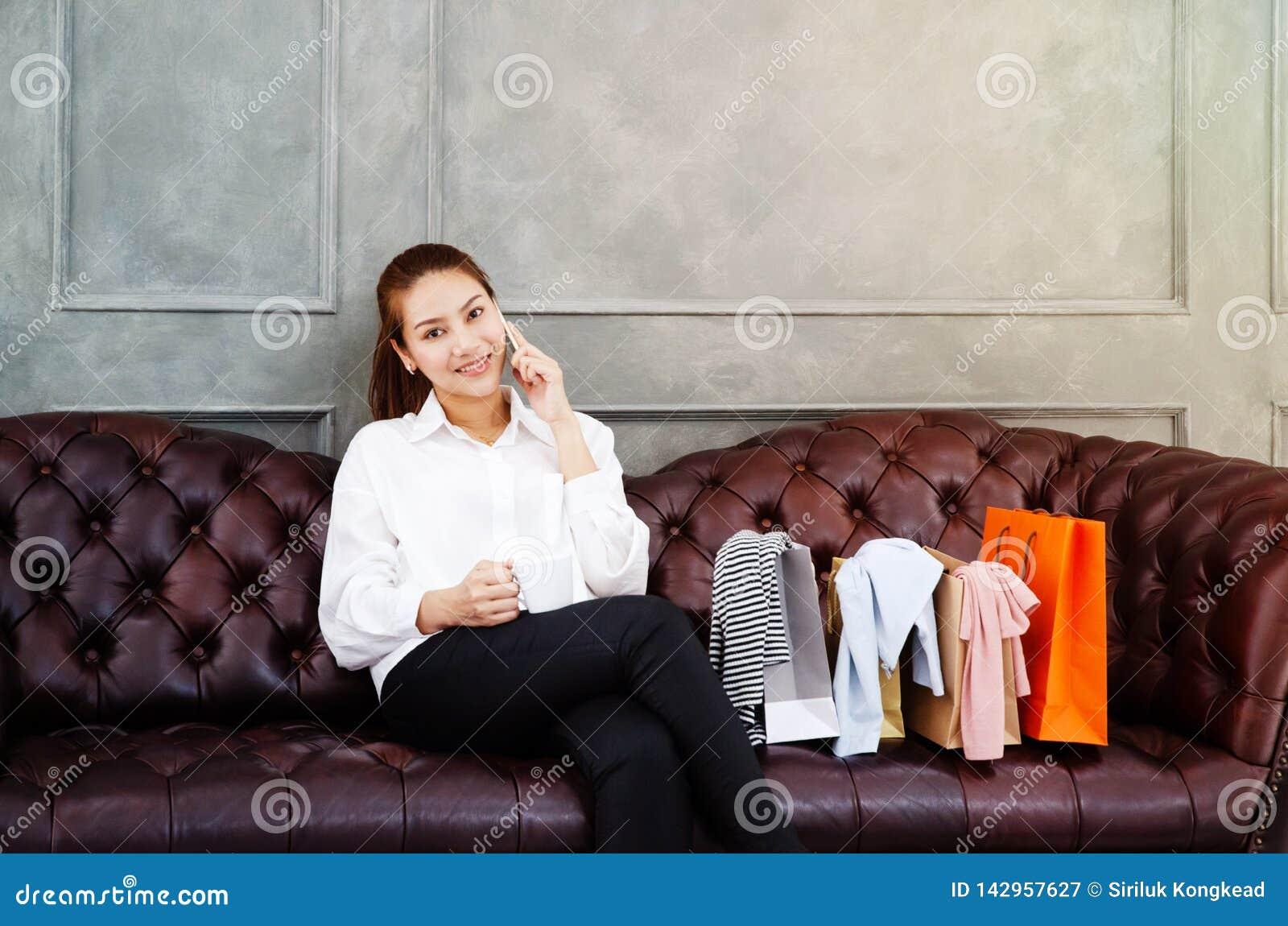 妇女是工作和愉快的 美丽的亚裔妇女微笑着 亚裔妇女与在沙发的灰色膝上型计算机一起使用在平均观测距离的屋子里