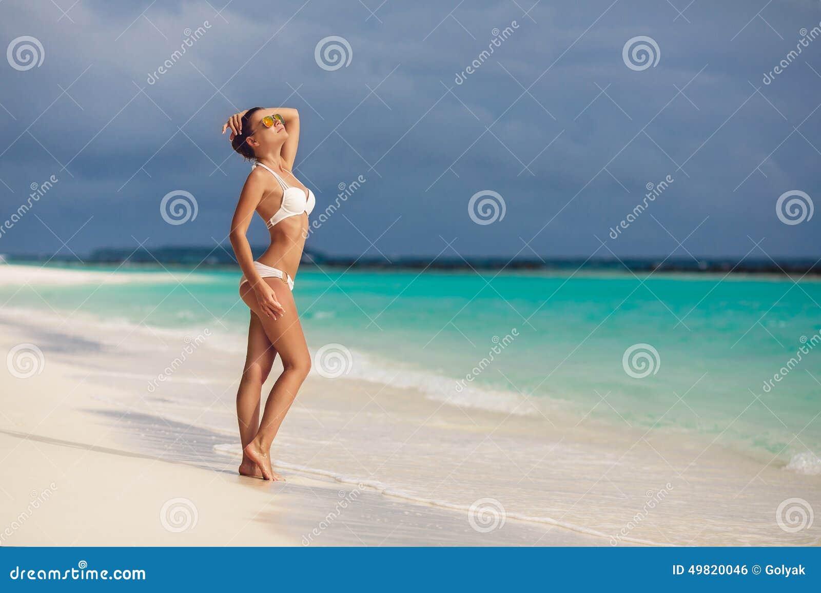 妇女晒黑在查寻的海滩的身分