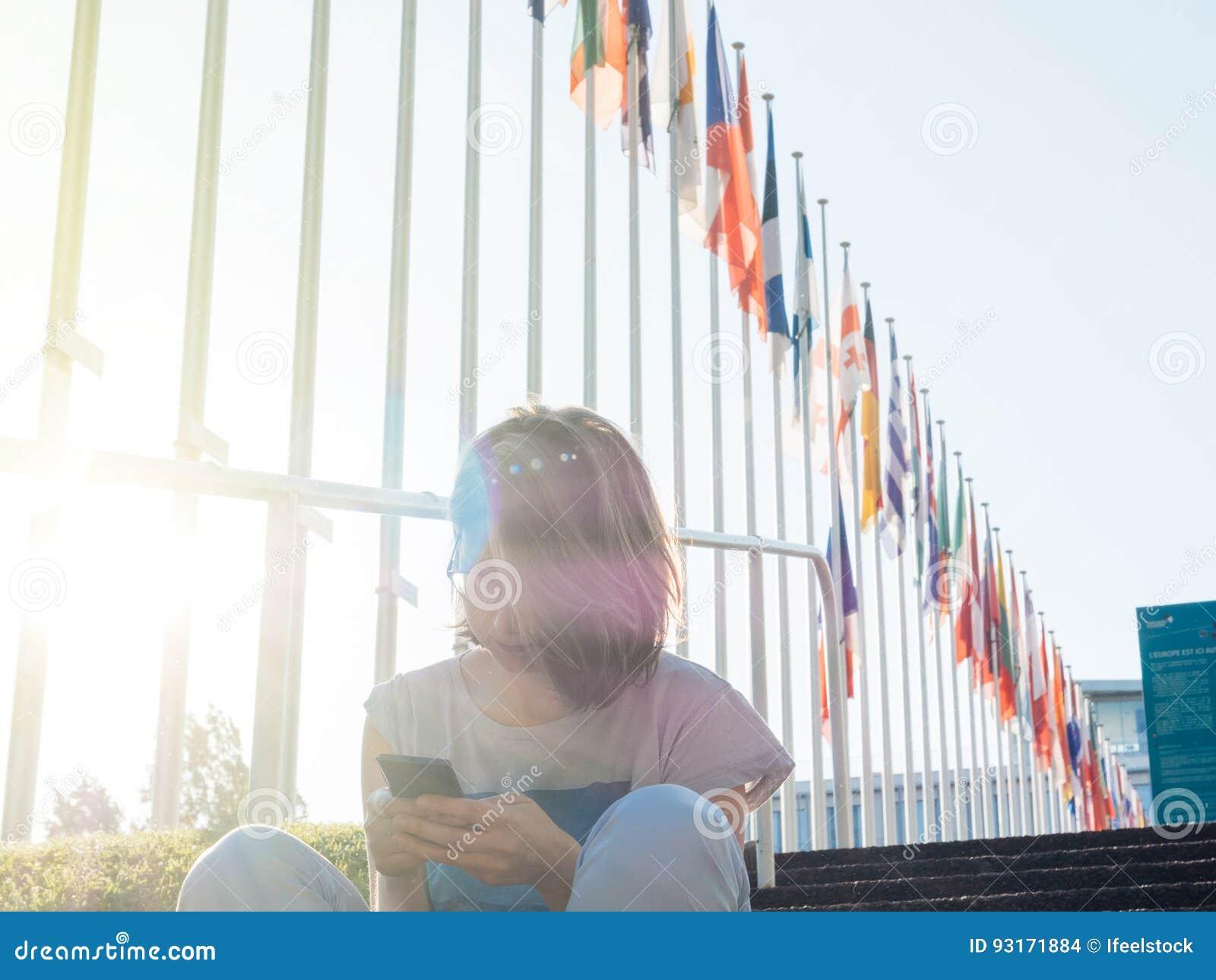 妇女有欧盟的读书智能手机和英国旗子飞行下半旗