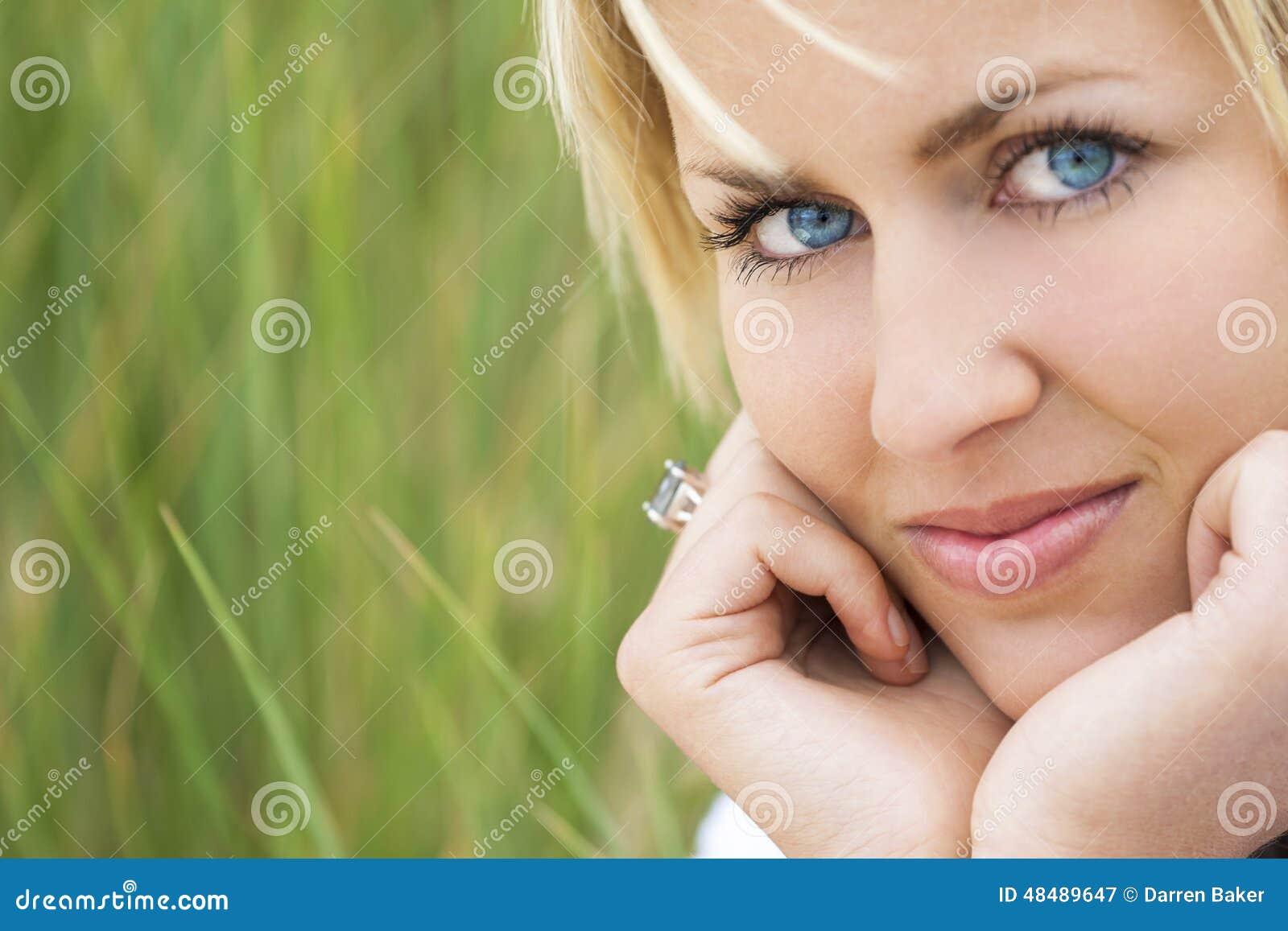 妇女有金发蓝眼睛绿色背景