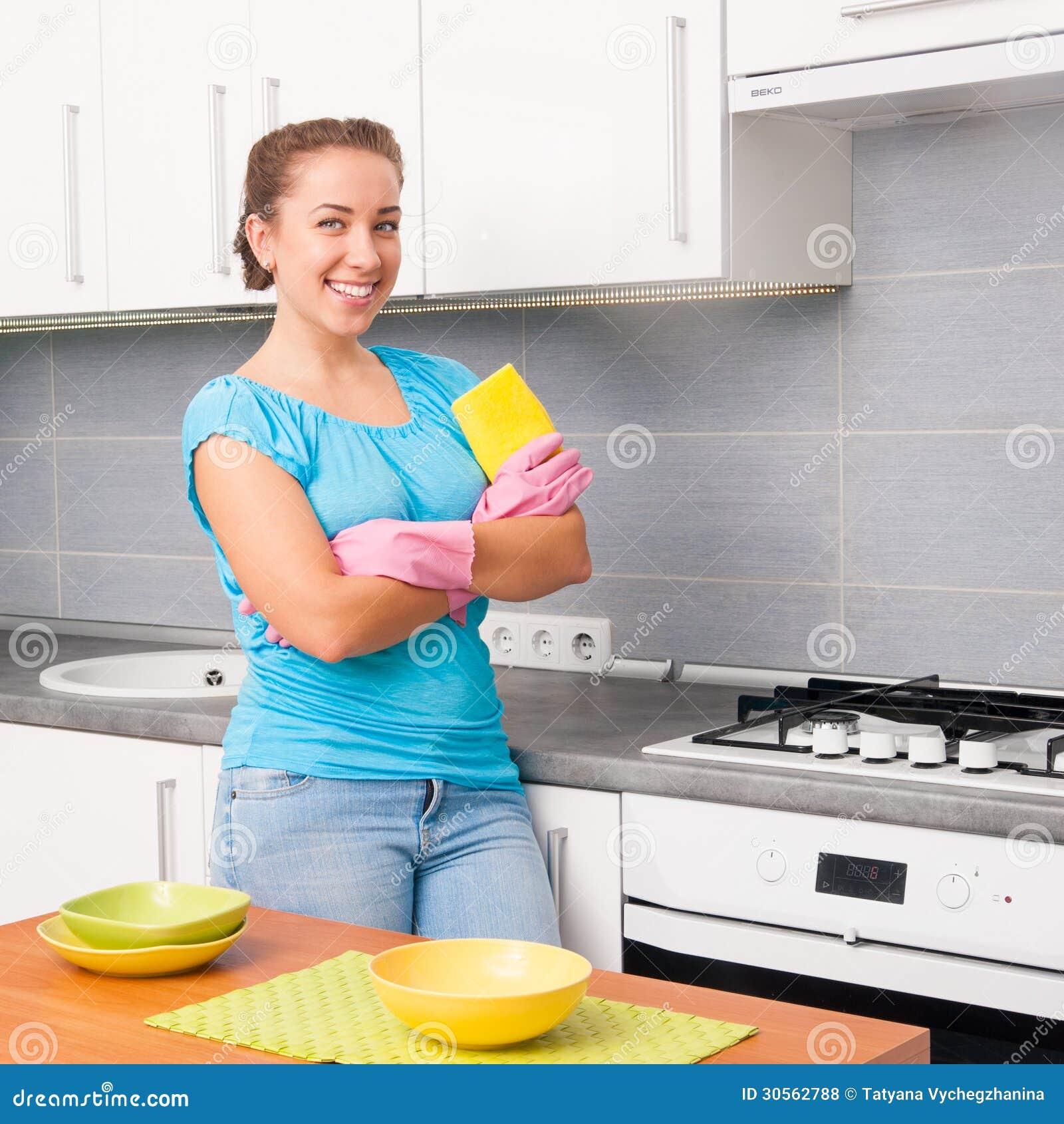 年轻人微笑的逗人喜爱的妇女在家清洗厨房.图片