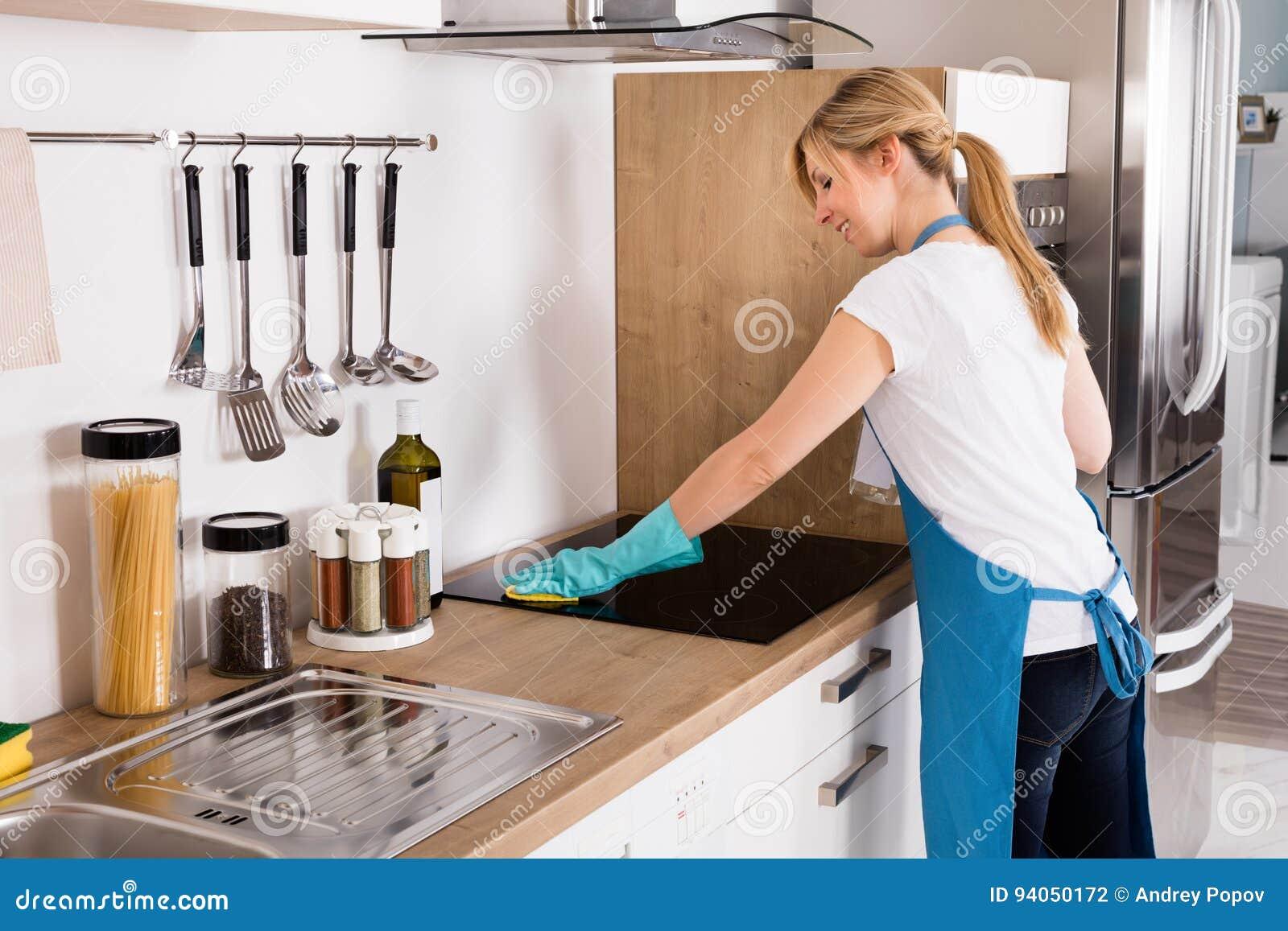 妇女清洁归纳火炉在厨房里