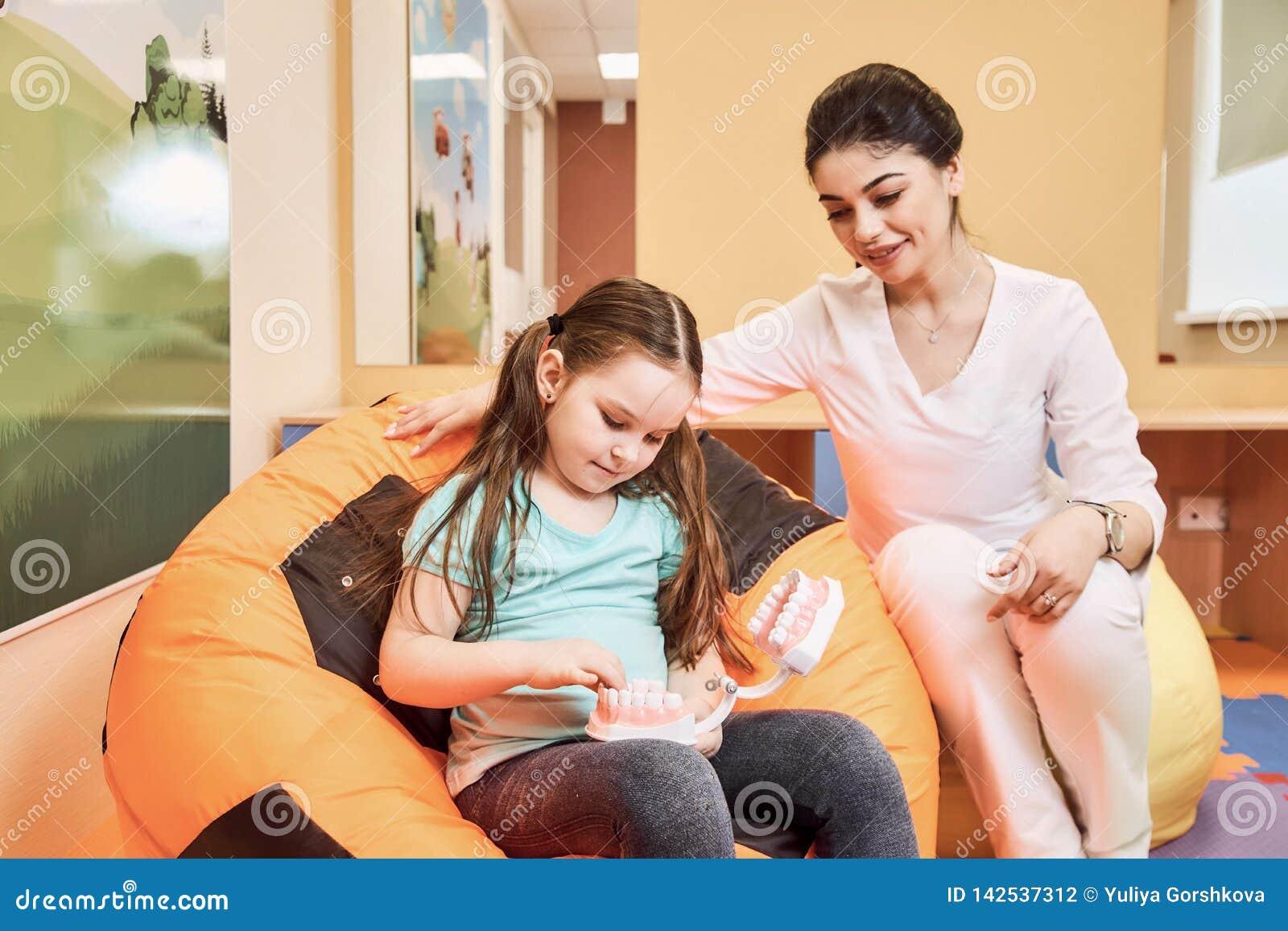 妇女牙医教女孩刷她的牙
