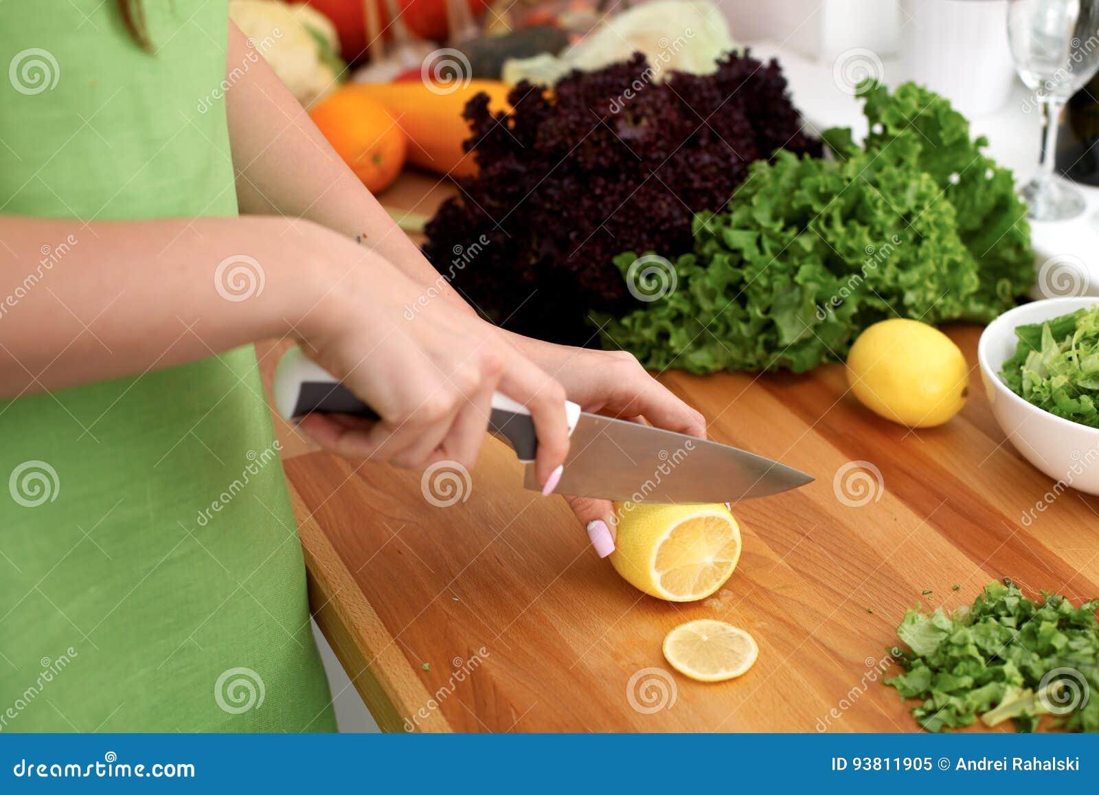妇女特写镜头在厨房里递烹调菜沙拉 主妇切柠檬 健康膳食和素食主义者概念