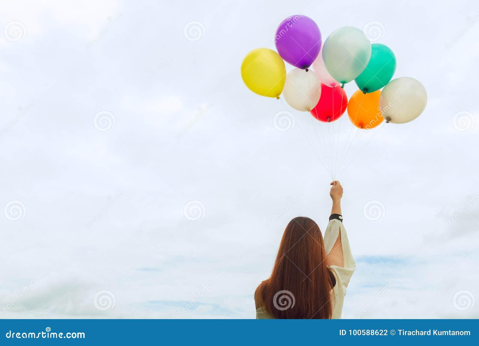 妇女生活方式概念-拿着一束有蓝天的色的气球的妇女手 葡萄酒口气过滤器颜色样式