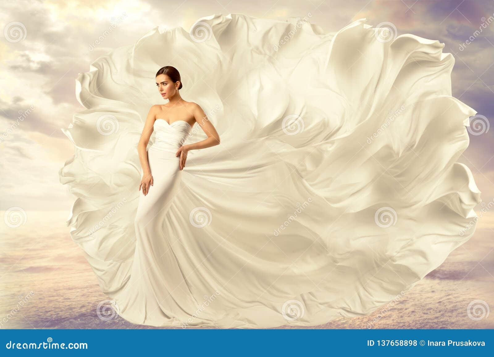 妇女白色礼服,在长的丝绸挥动的褂子,在风的飞行的振翼的织品的时装模特儿
