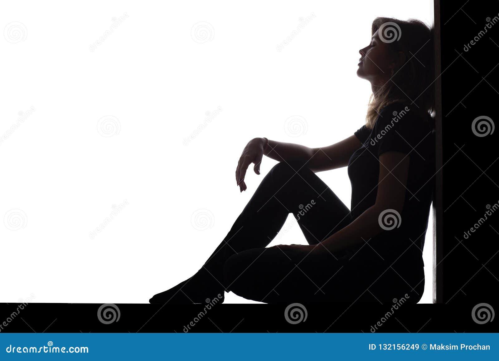 妇女的剪影坐在一个角落的地板在白色被隔绝的背景,一个哀伤的女孩考虑问题的,概念
