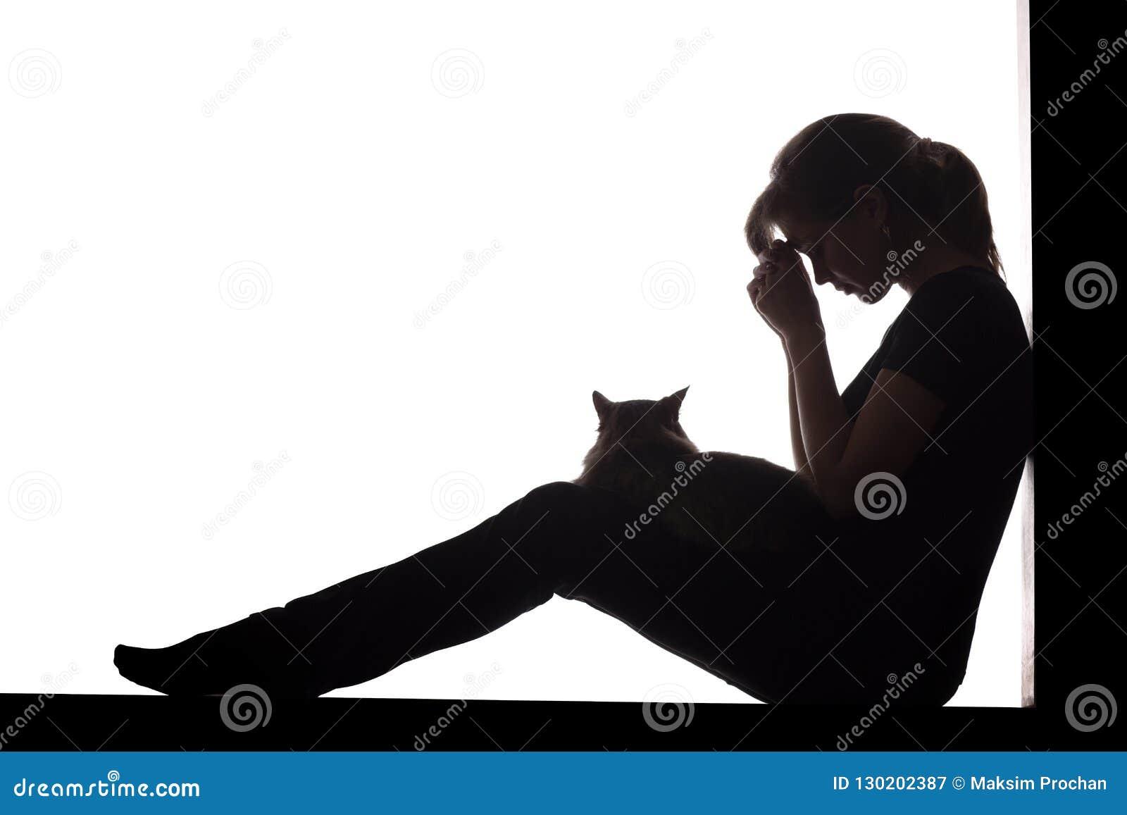妇女的剪影坐在白色被隔绝的背景的地板与在她的胳膊的一只猫,一哀伤女孩祈祷