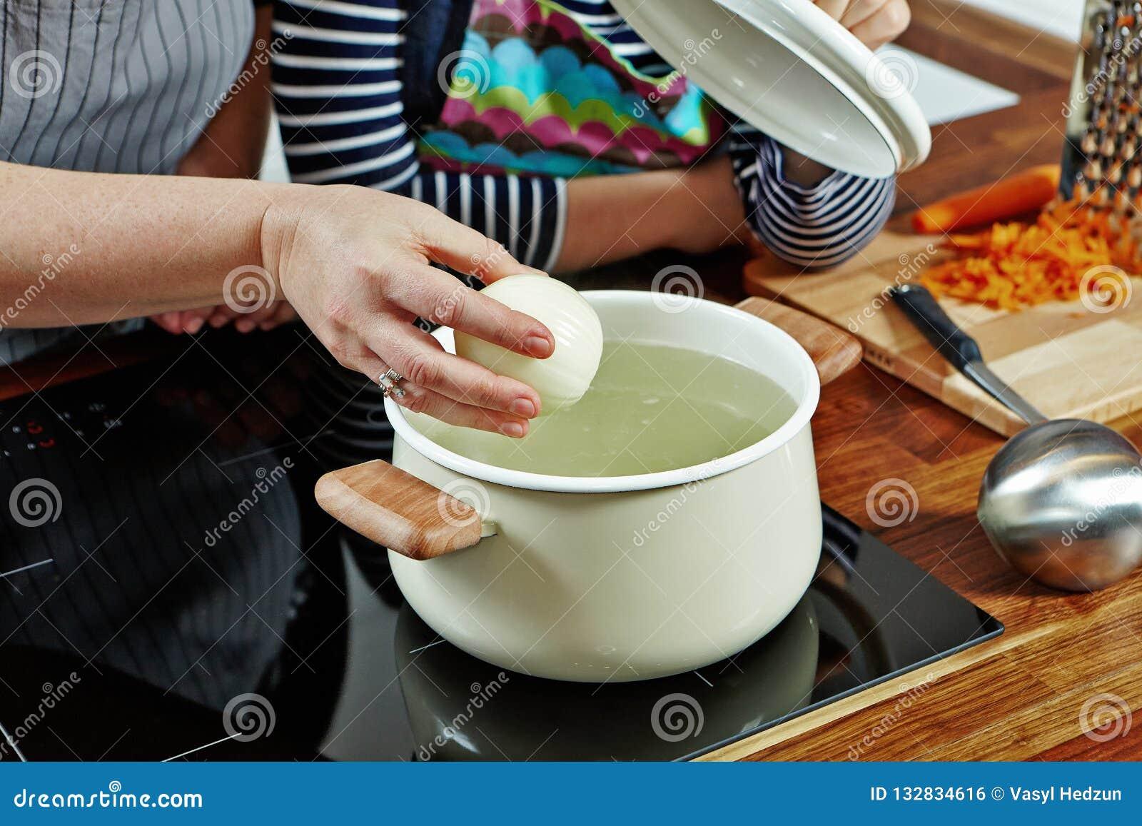 妇女的手以放它的未加工的葱入开水 在黑火炉的被打开的白色平底深锅 烹调汤