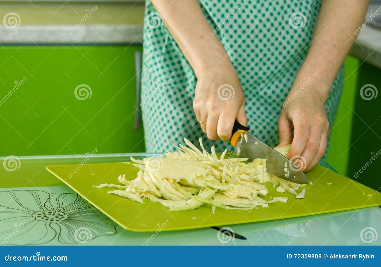 妇女的手切了在绿色黑板的圆白菜